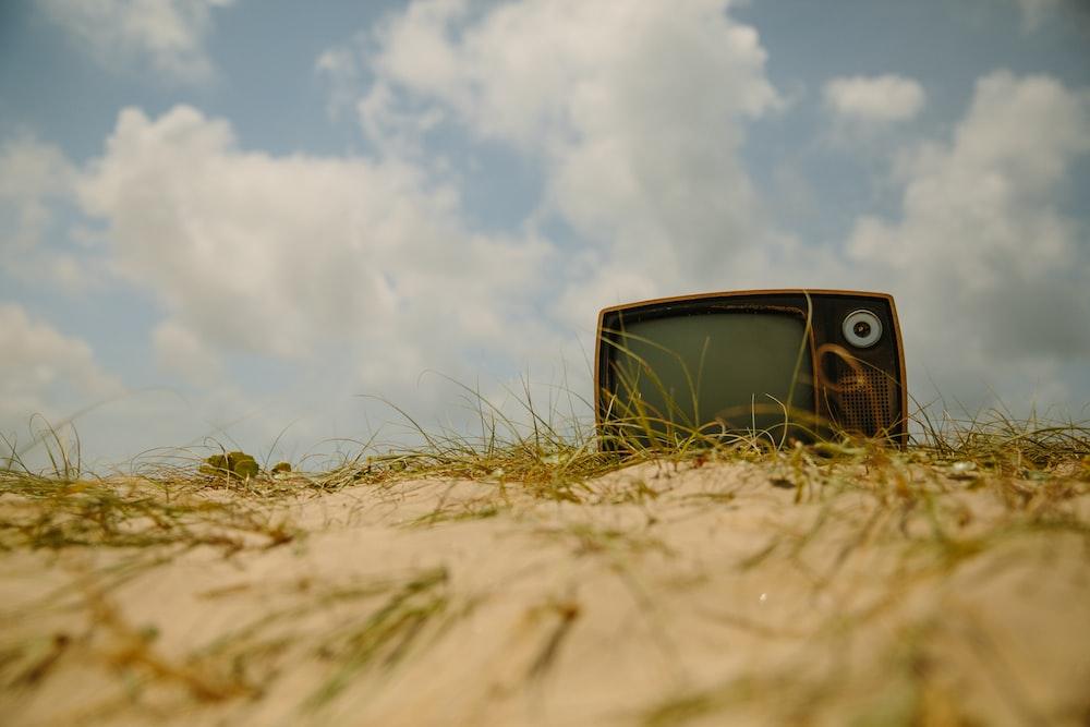 vintage black and brown TV on brown soil at daytime