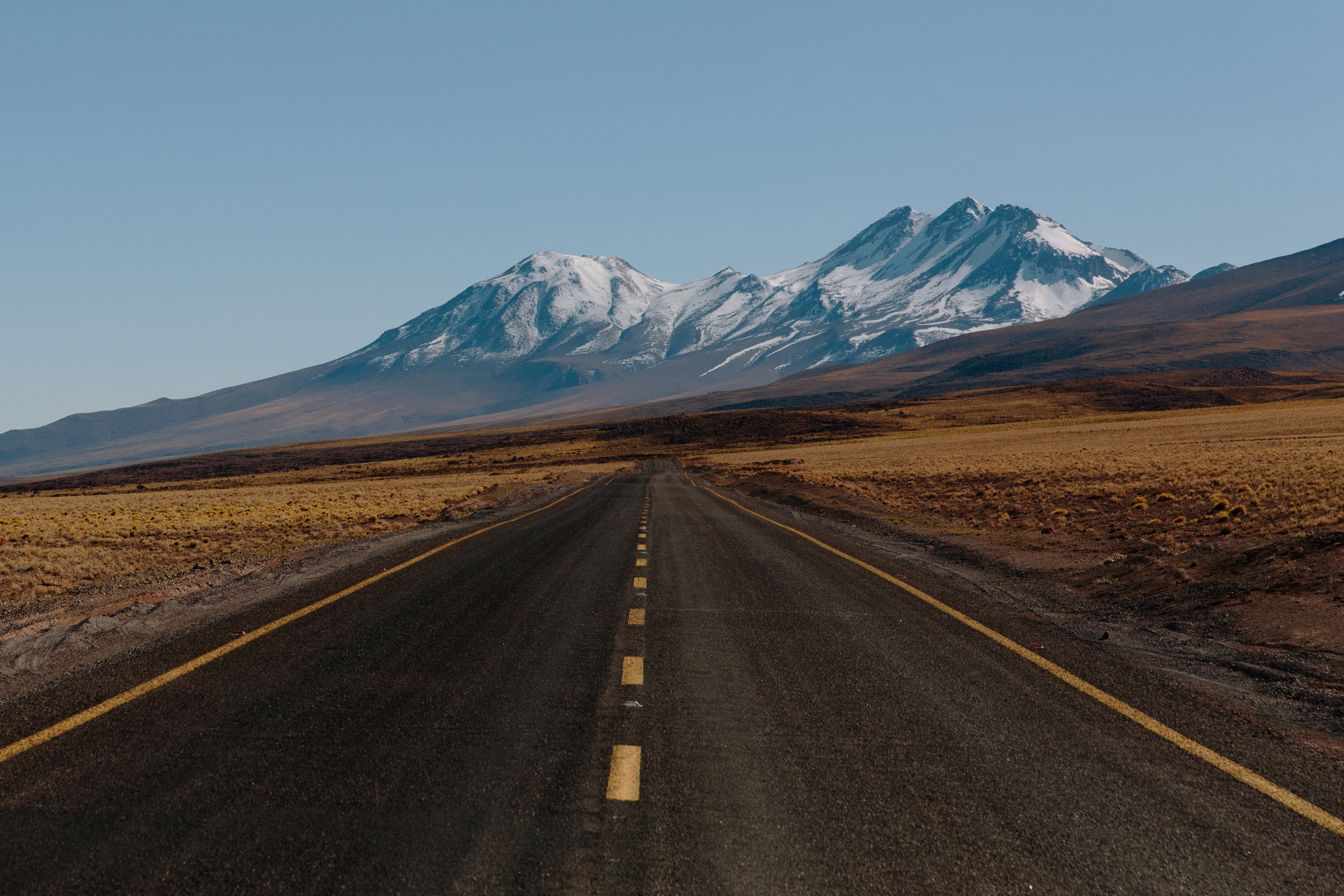 A highway surrounded by an arid field leading to a snowy mountain in San Pedro de Atacama