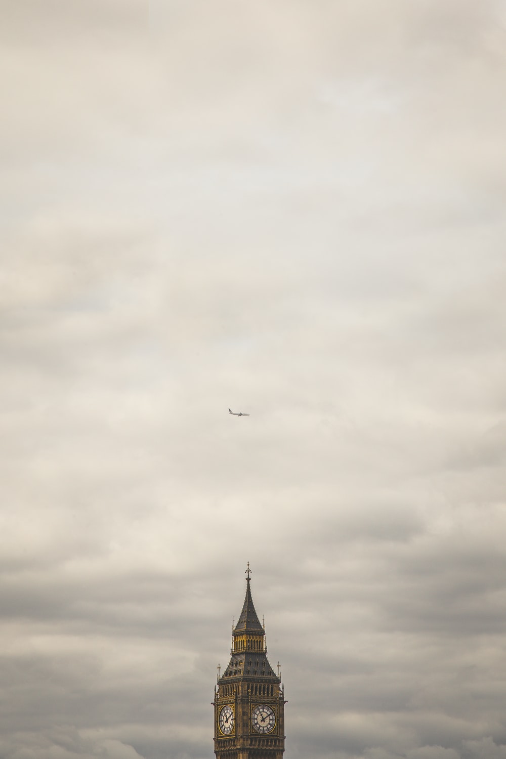 Elizabeth Tower under of white airliner during heavy clouds