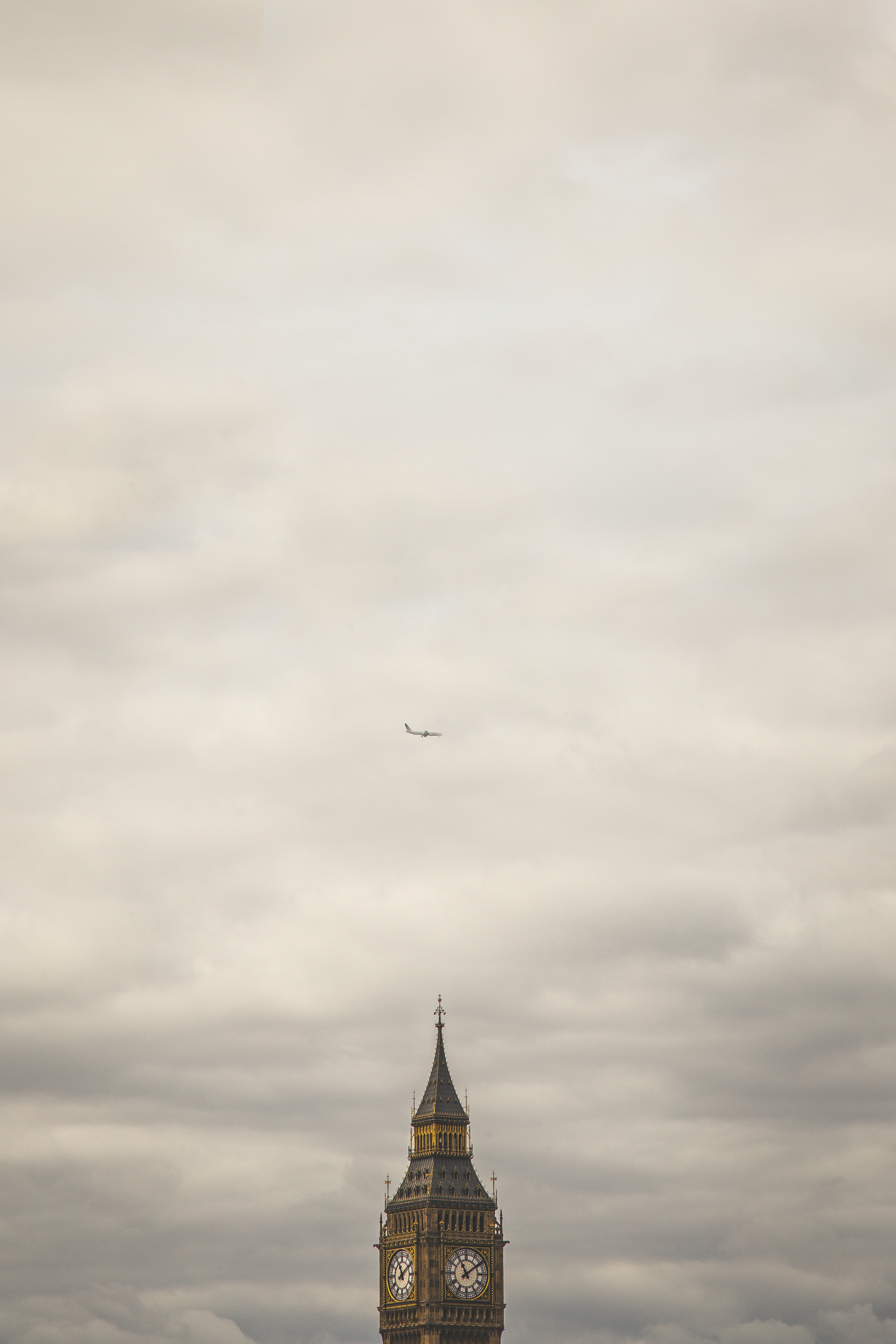 A plane in the sky above the Big Ben clock tower in London