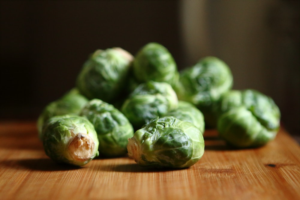 shallow depth of fields photography of green vegetable on brown wooden panel