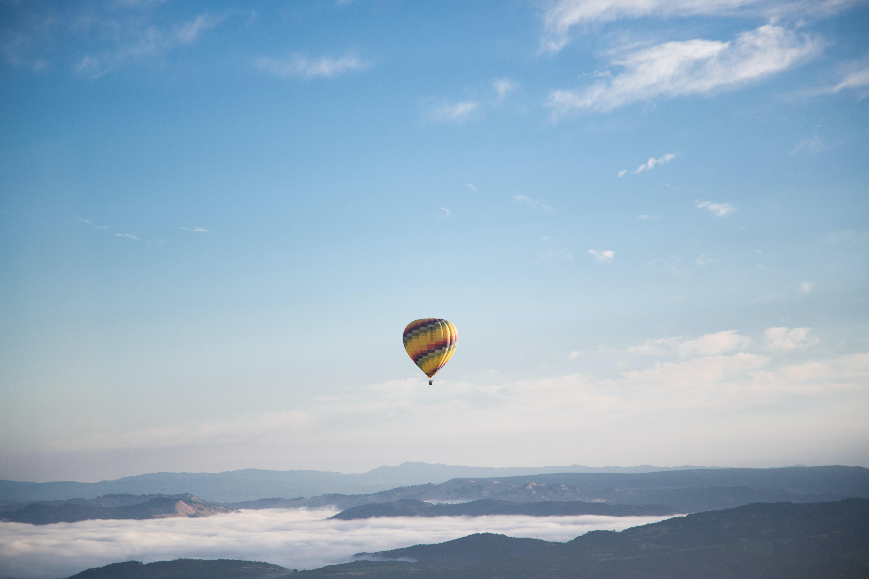 Hot air balloon flying over a foggy mountain landscape