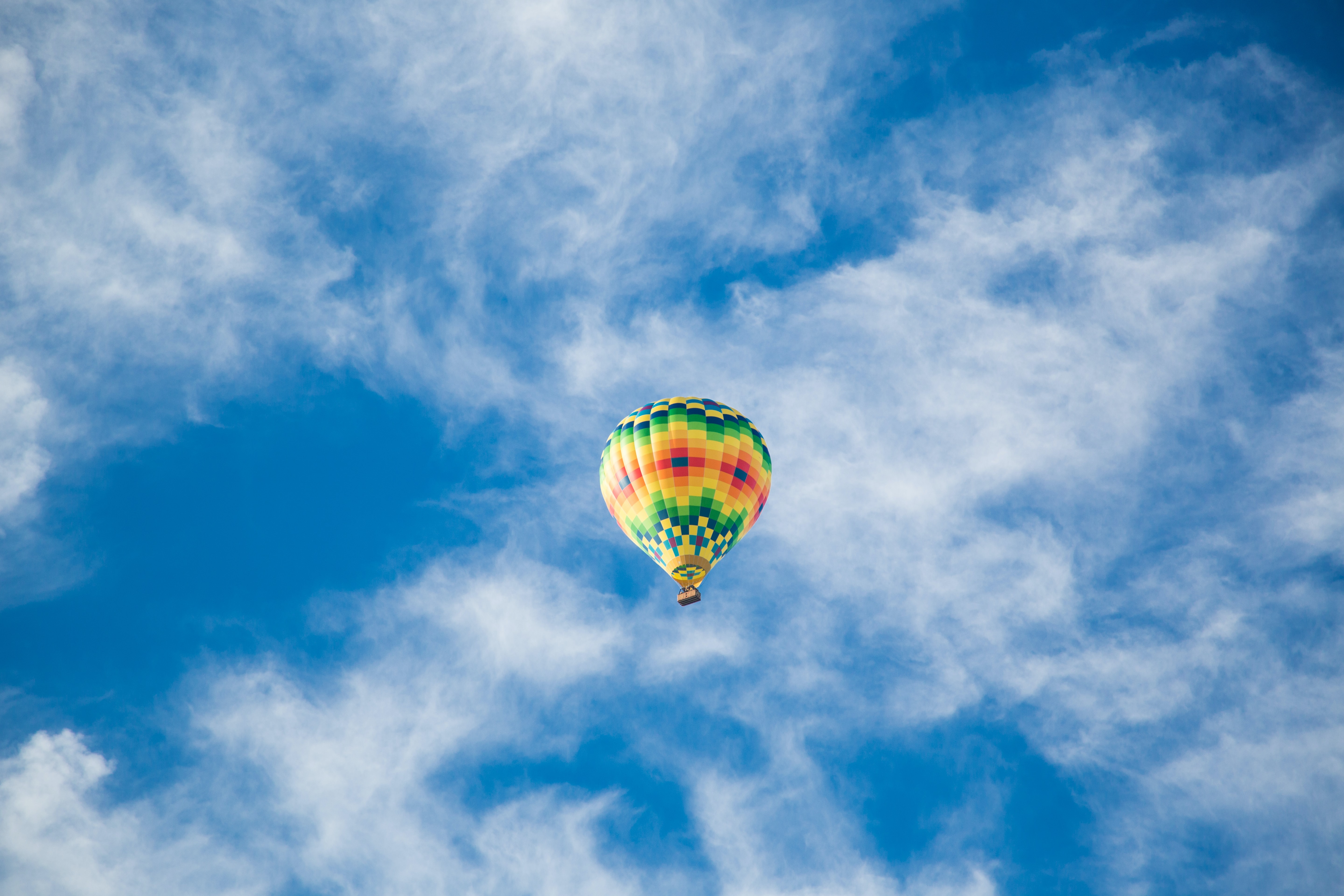 Colorful hot air balloon flies across a bright blue sky