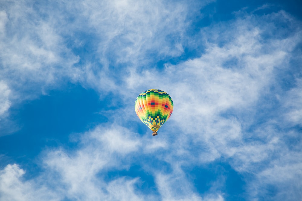 yellow, green, and black hot air balloon on sky
