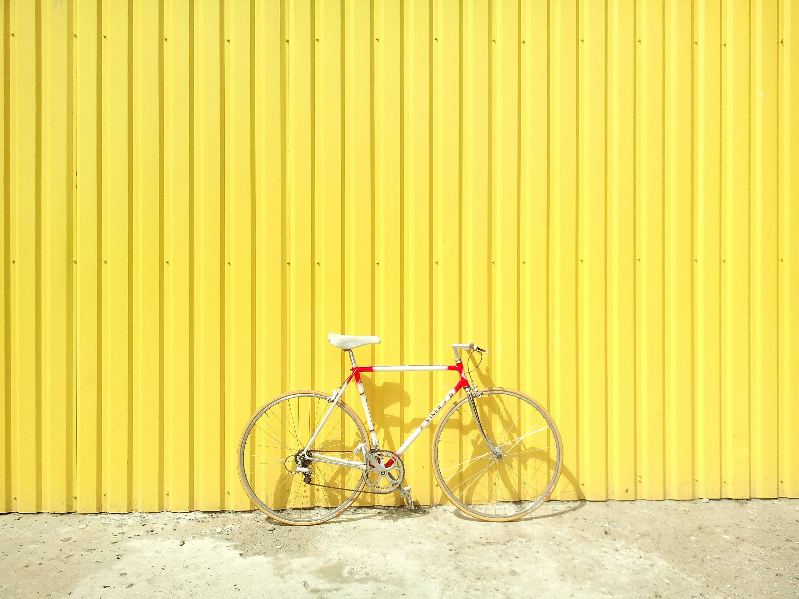 A vintage bicycle leaned against bright yellow wall