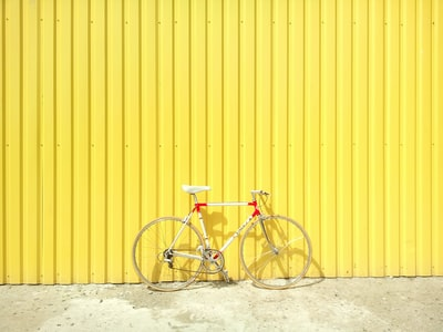 white and red hardtail bike on yellow wall bright zoom background