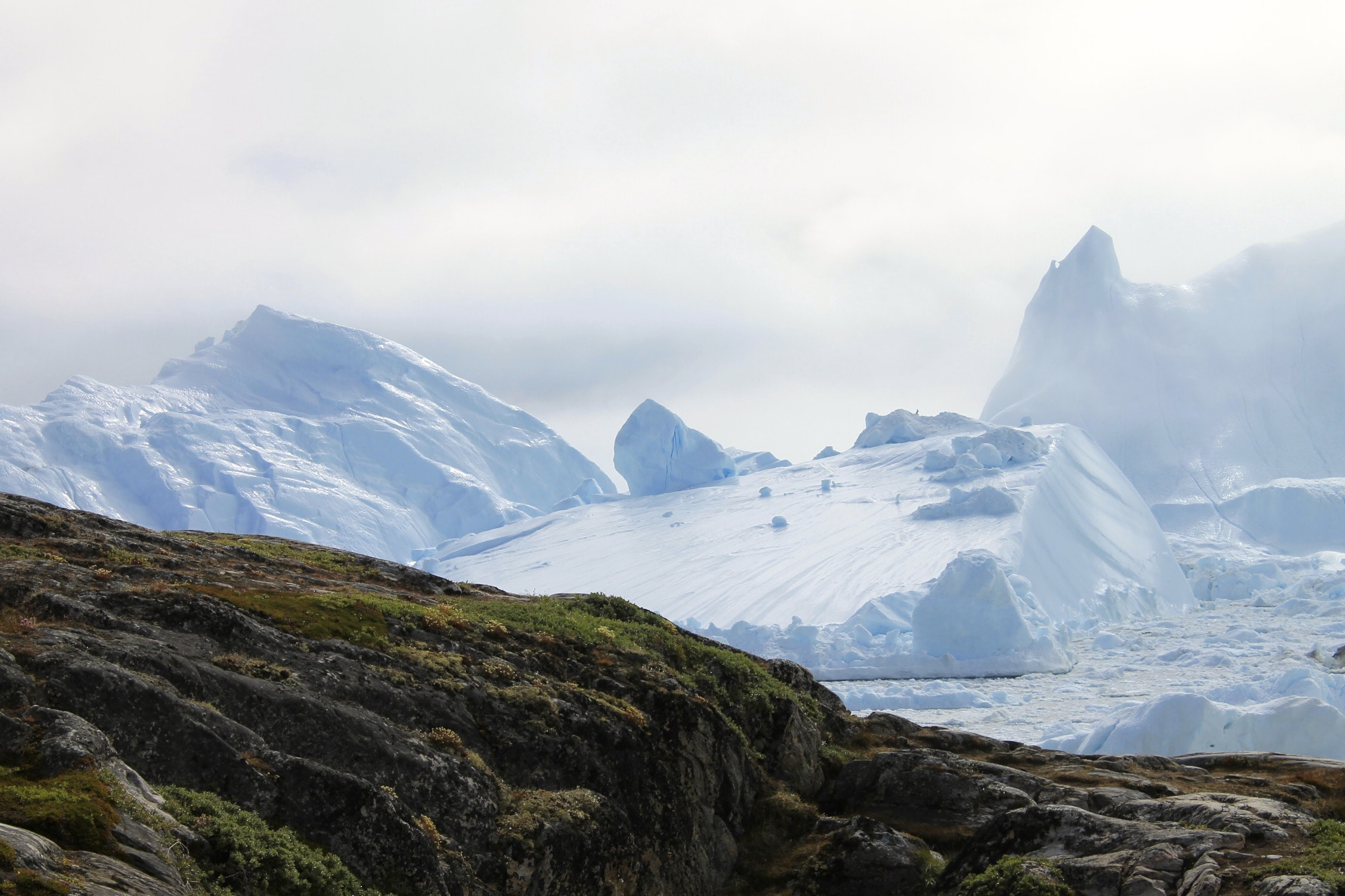 A rocky ridge against the icy glaciers of Ilulissat, Greenland