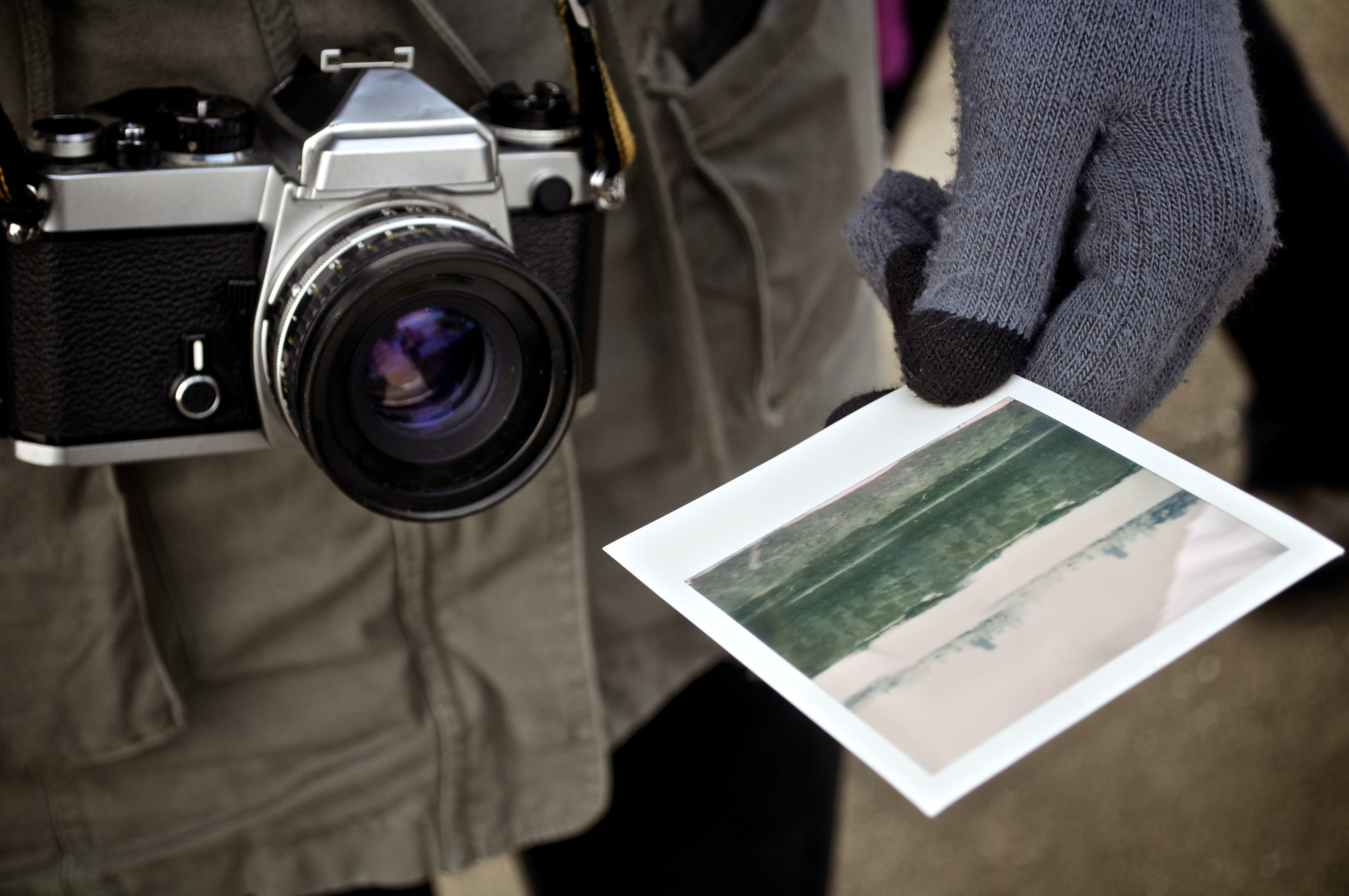 A close-up of a camera and a man wearing gloves holding a photograph.