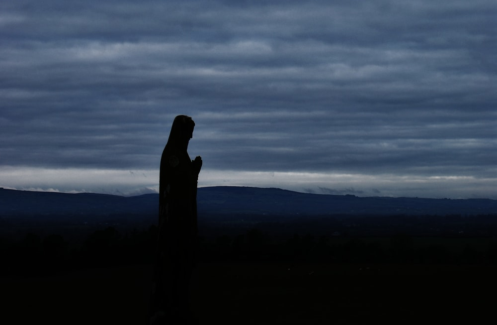 silhouette of person under cloudy sky