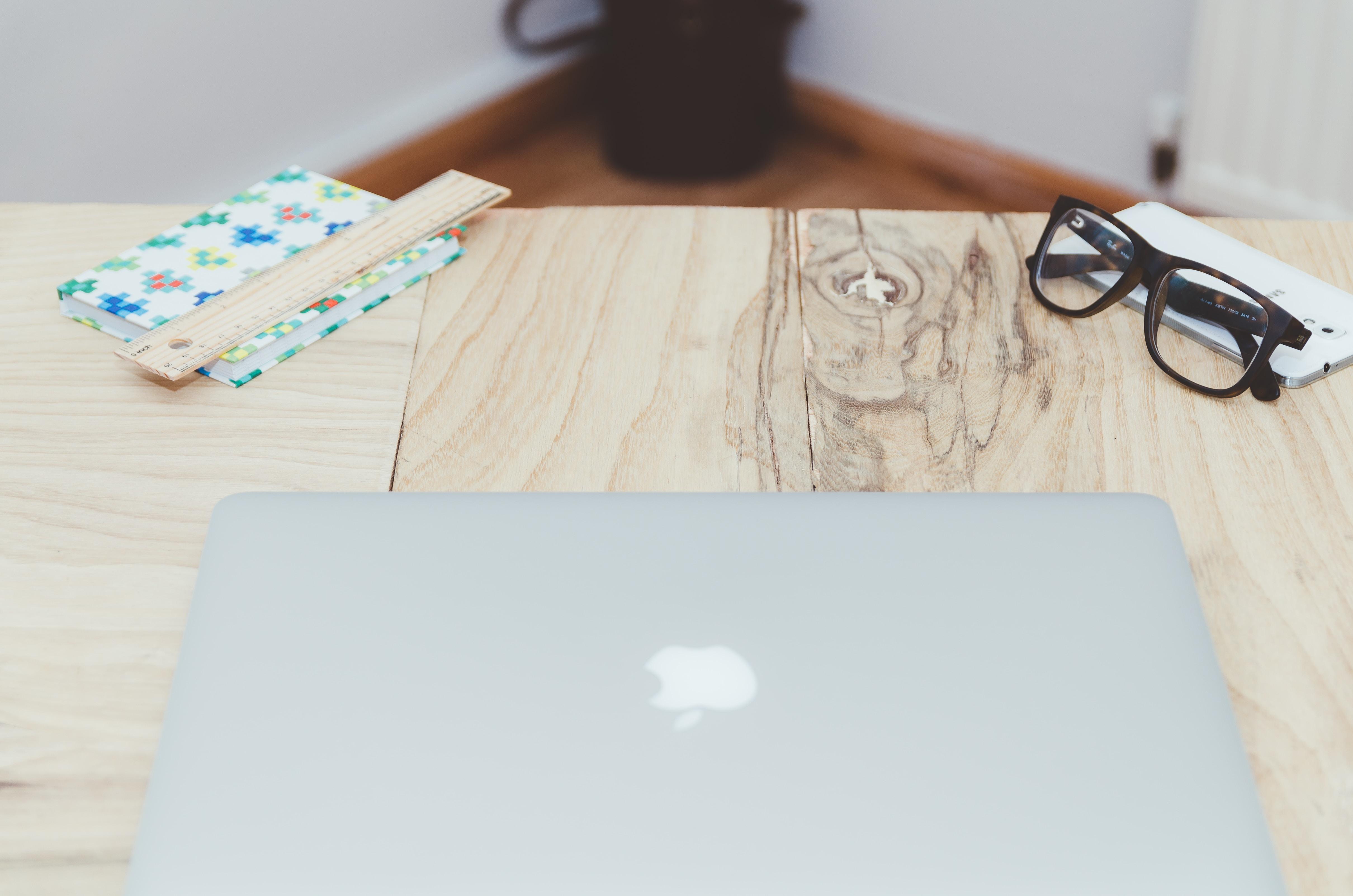 silver MacBook on beige table