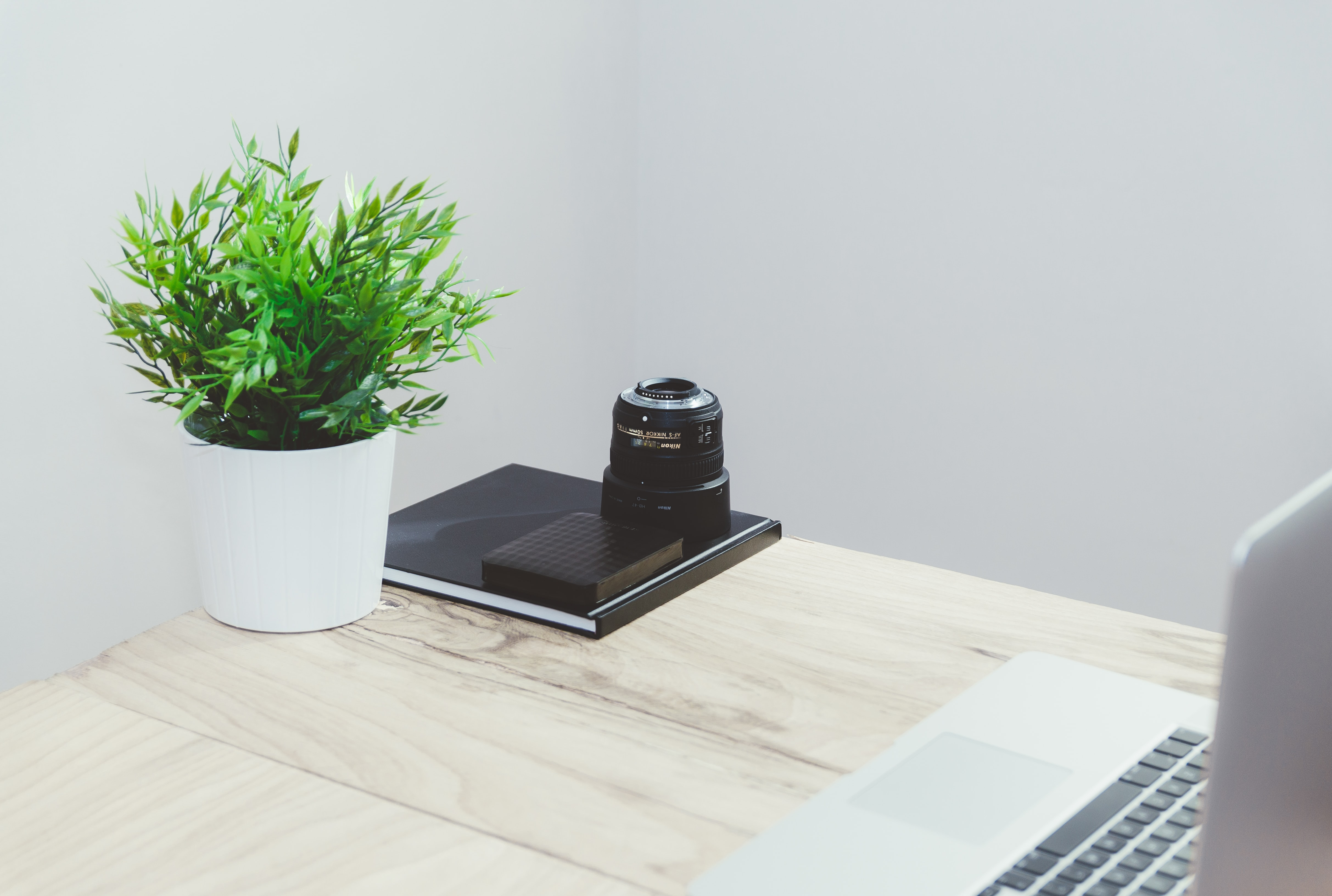 A zoom lens, a portable drive and a notebook at the edge of a table next to a potted plant
