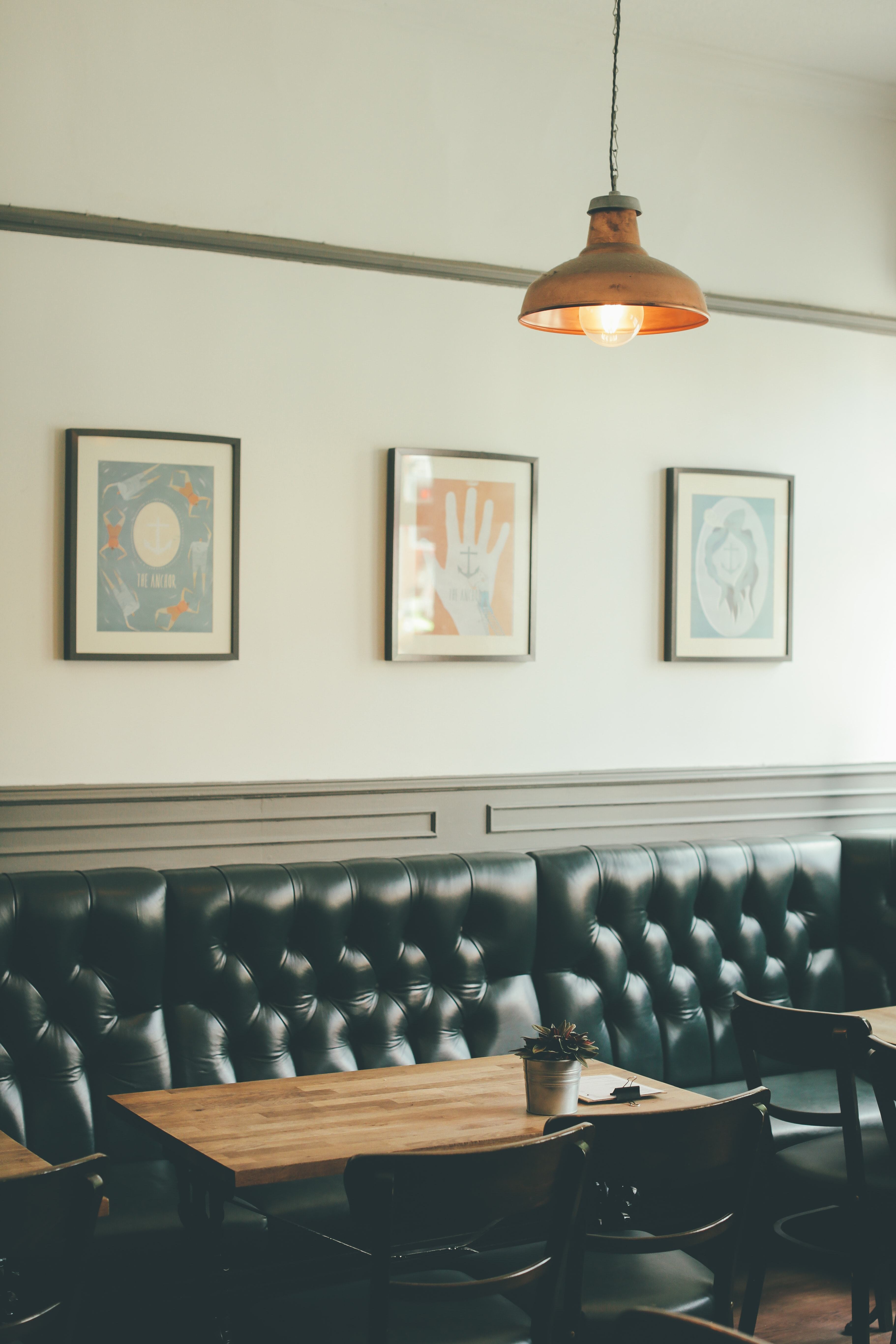 Tables next to a padded leather sofa in a café