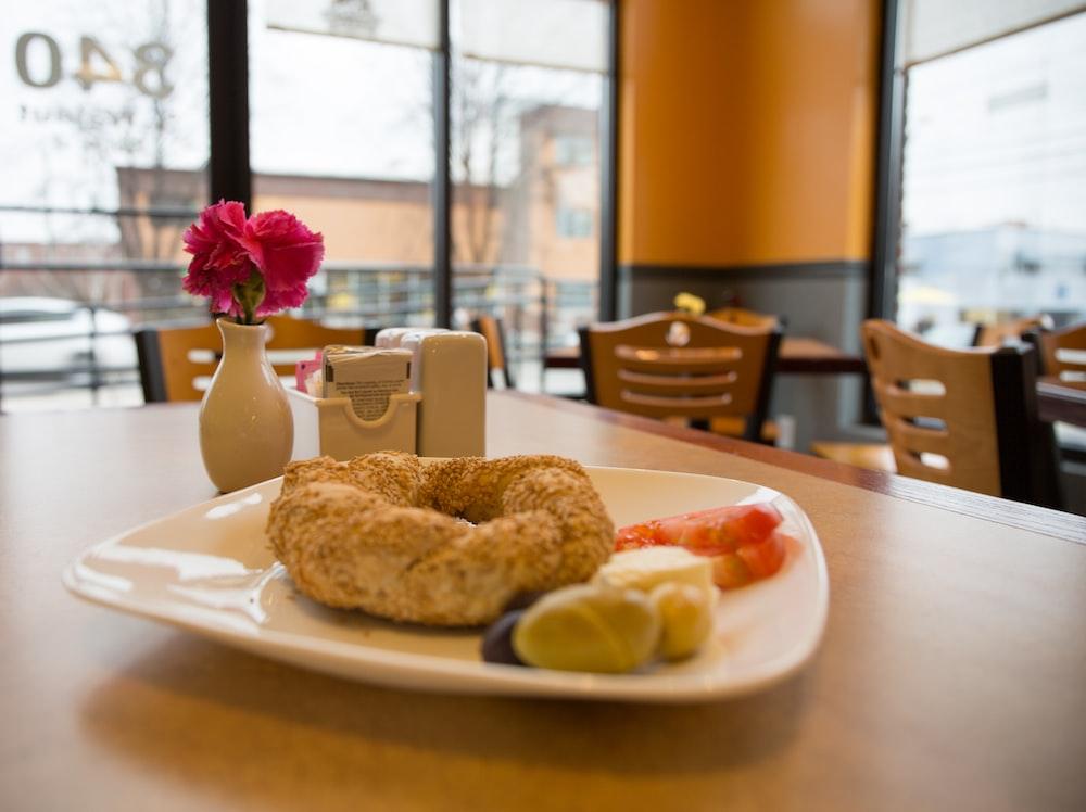 doughnut on white ceramic saucer on table