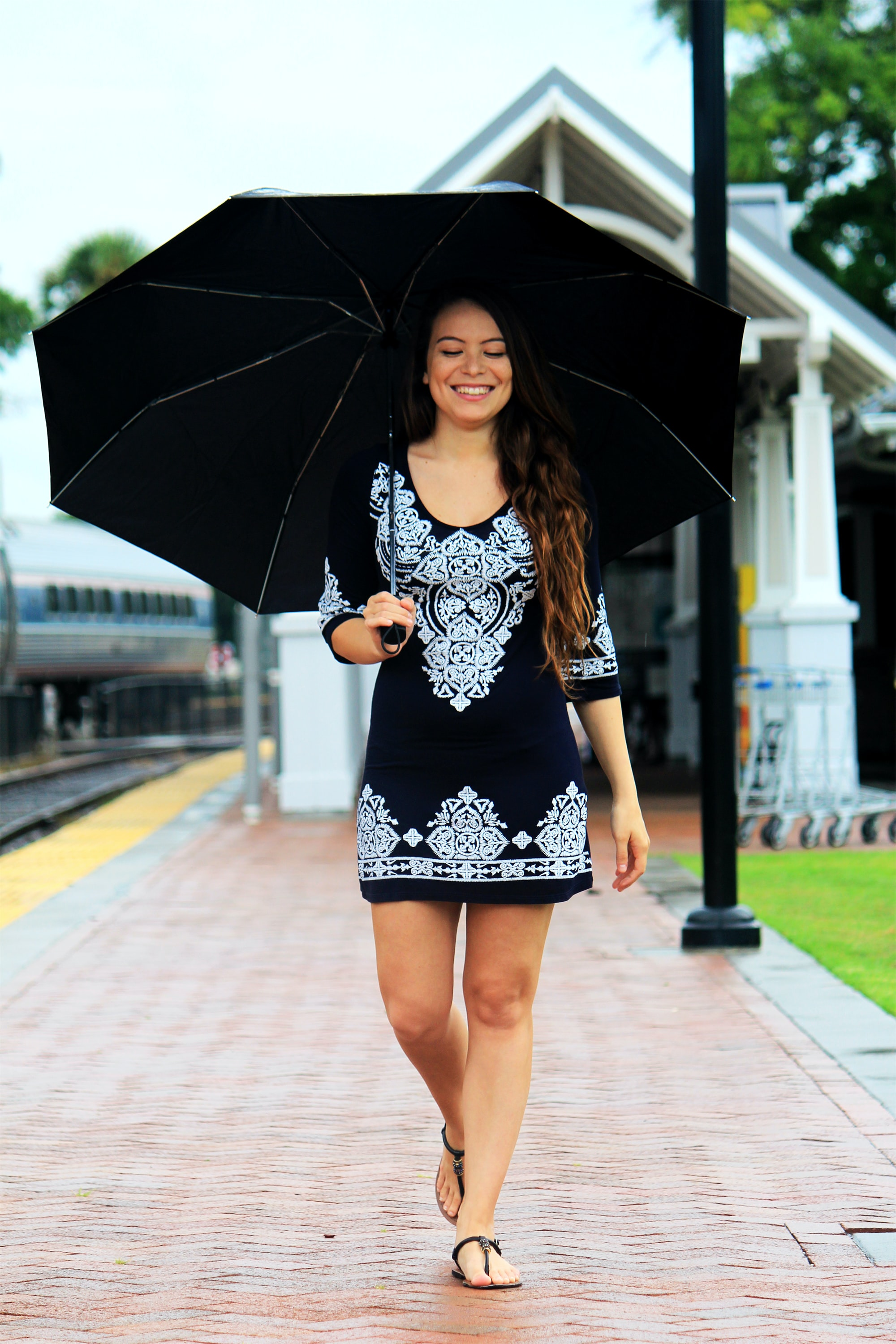 Smiling woman in black dress with closed eyes walks along a brick path, holding an umbrella