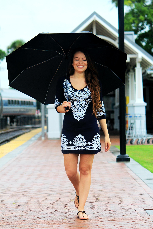 woman walking on brown pathway while holding black umbrella