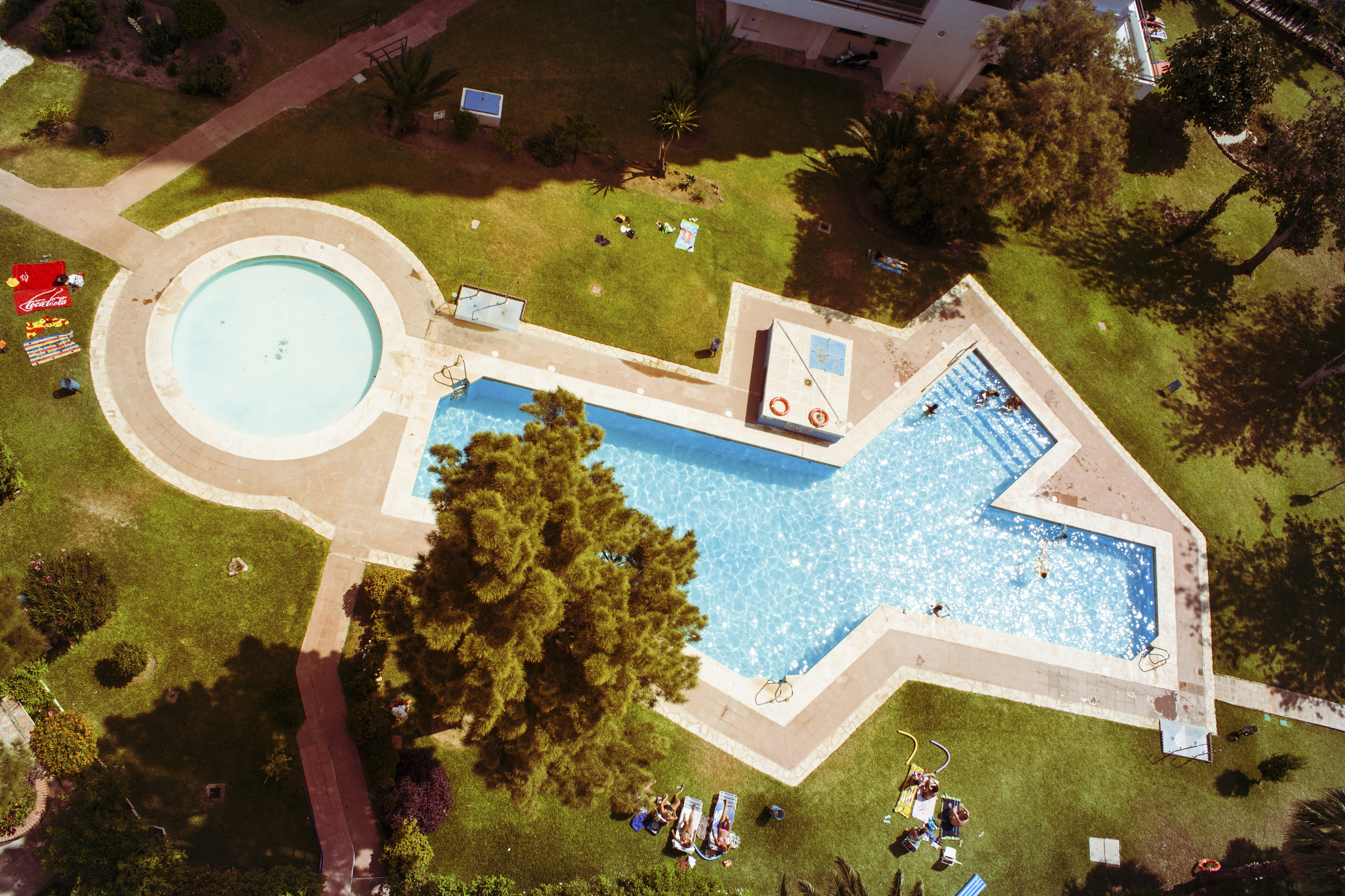 Drone view of pool in shape of X and O with swimming and sunbathing people