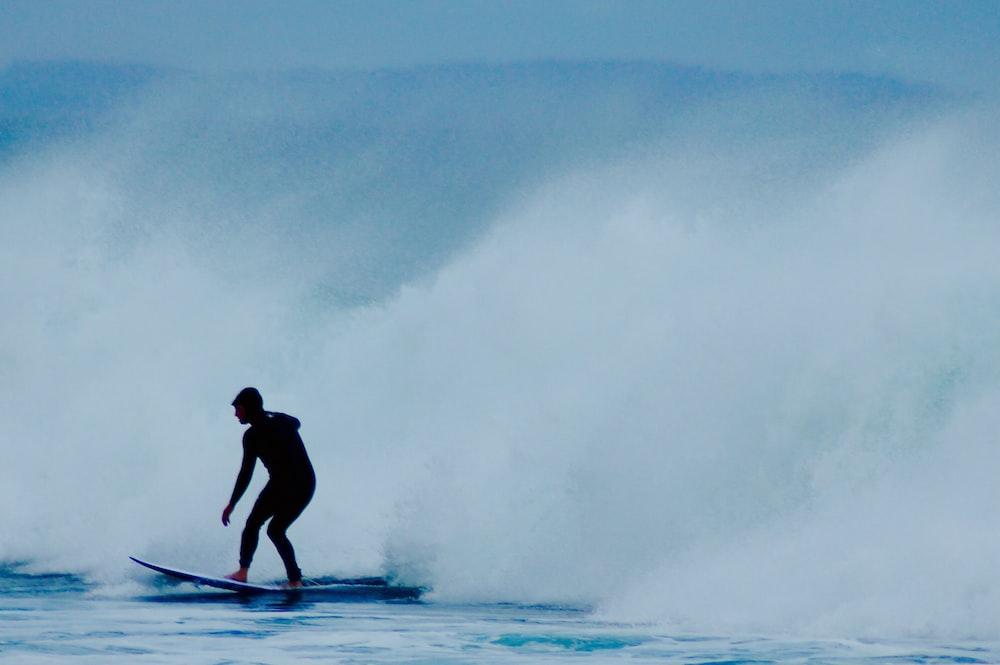 man riding surfboard near wave