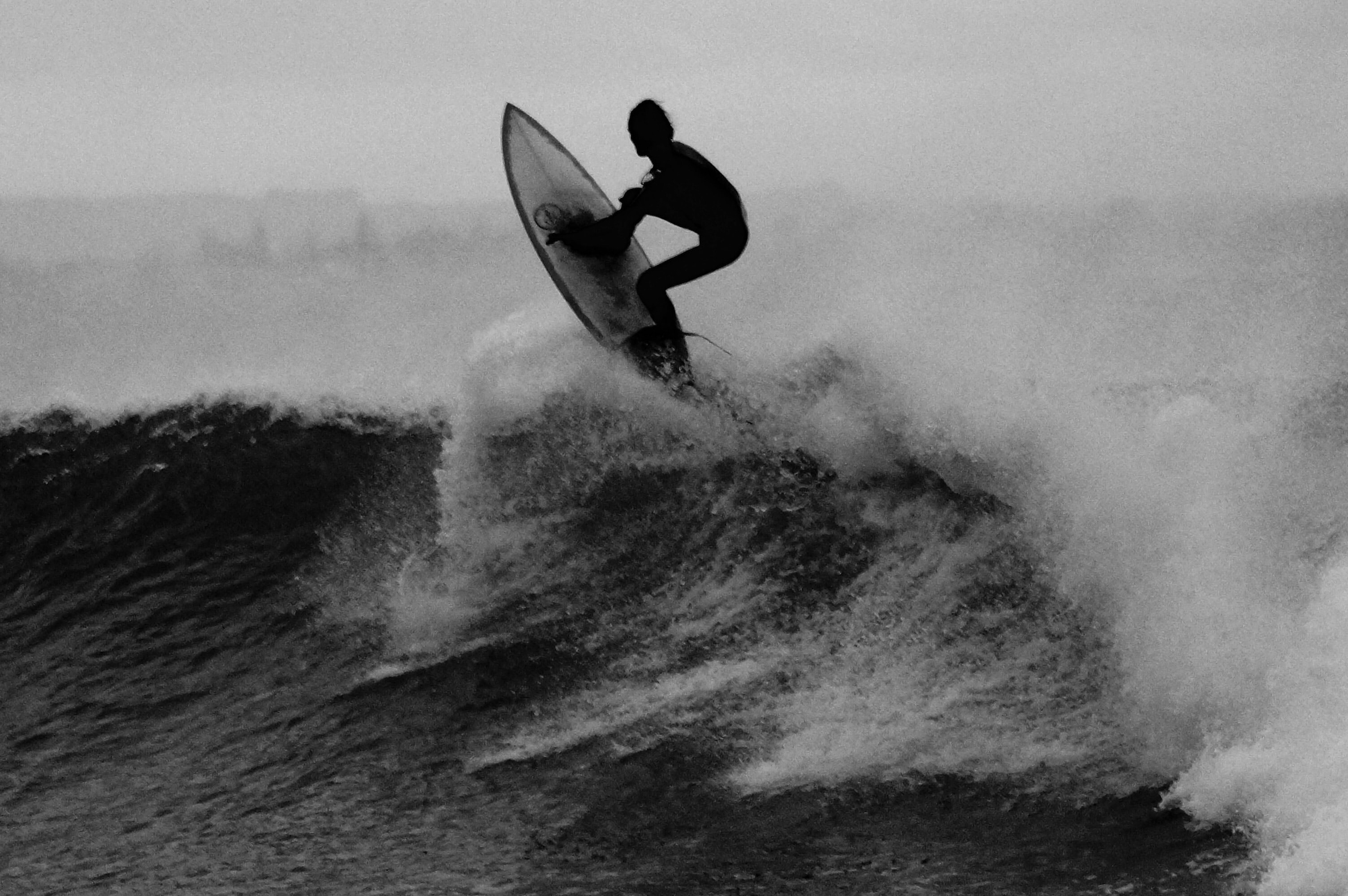 A black and white photo of a surfer catching waves at Point Leo