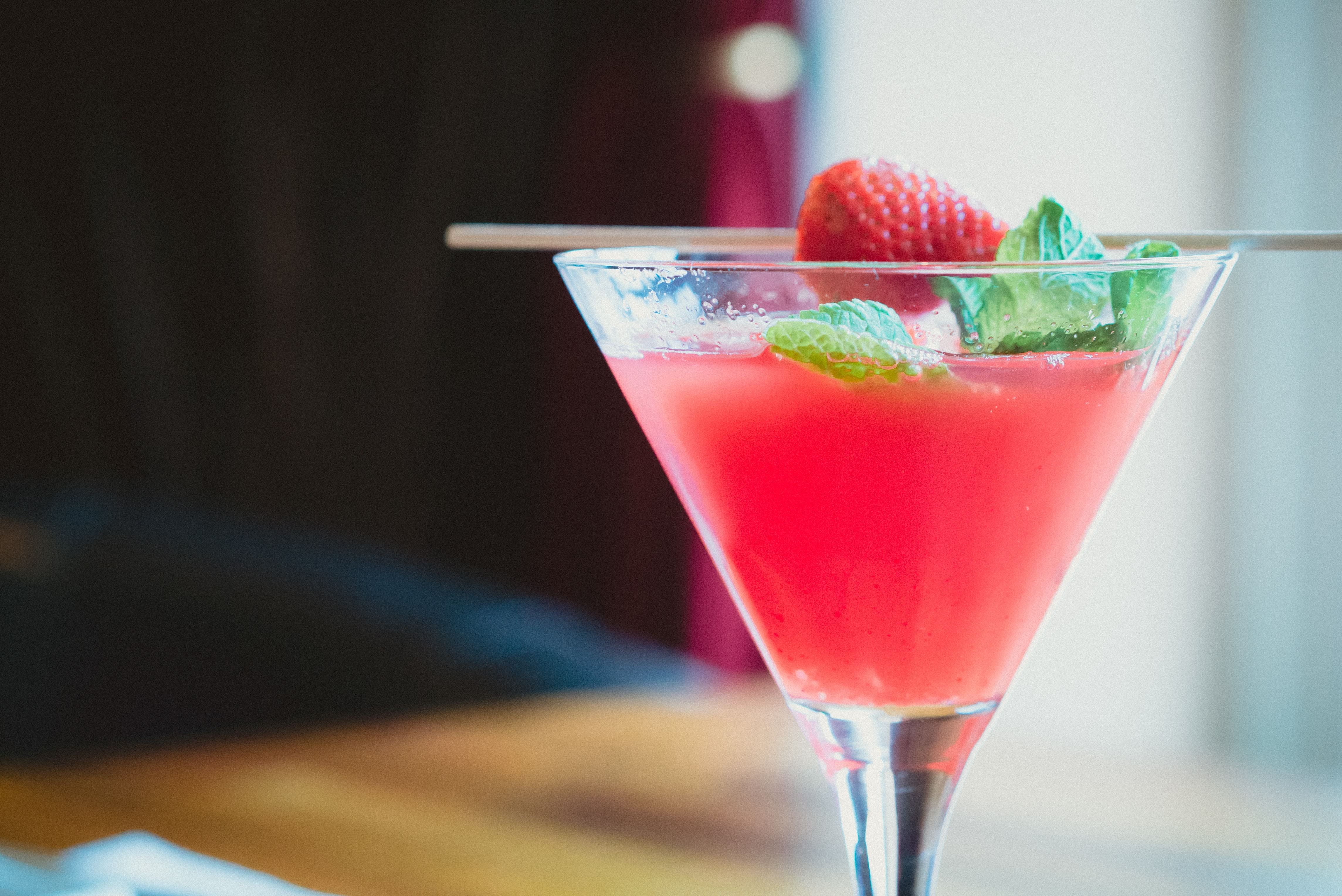 Macro view of a strawberry cocktail drink in a glass cup and a straw in it