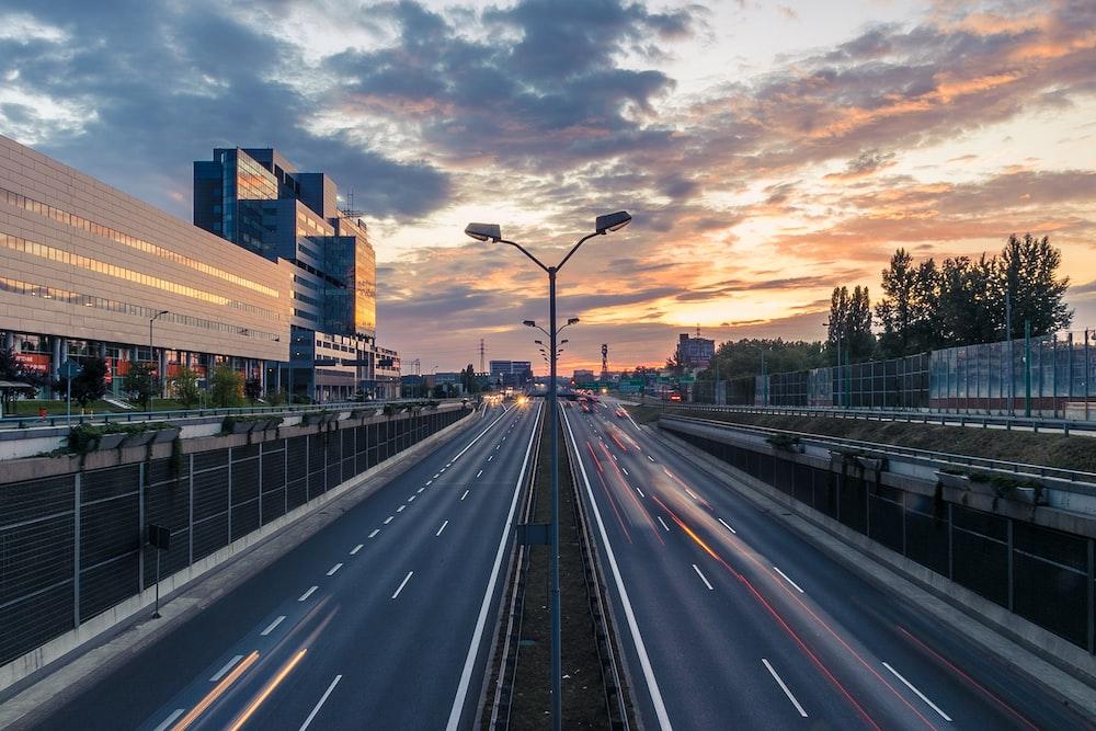 timelapse photo of 2-lane road under golden sky