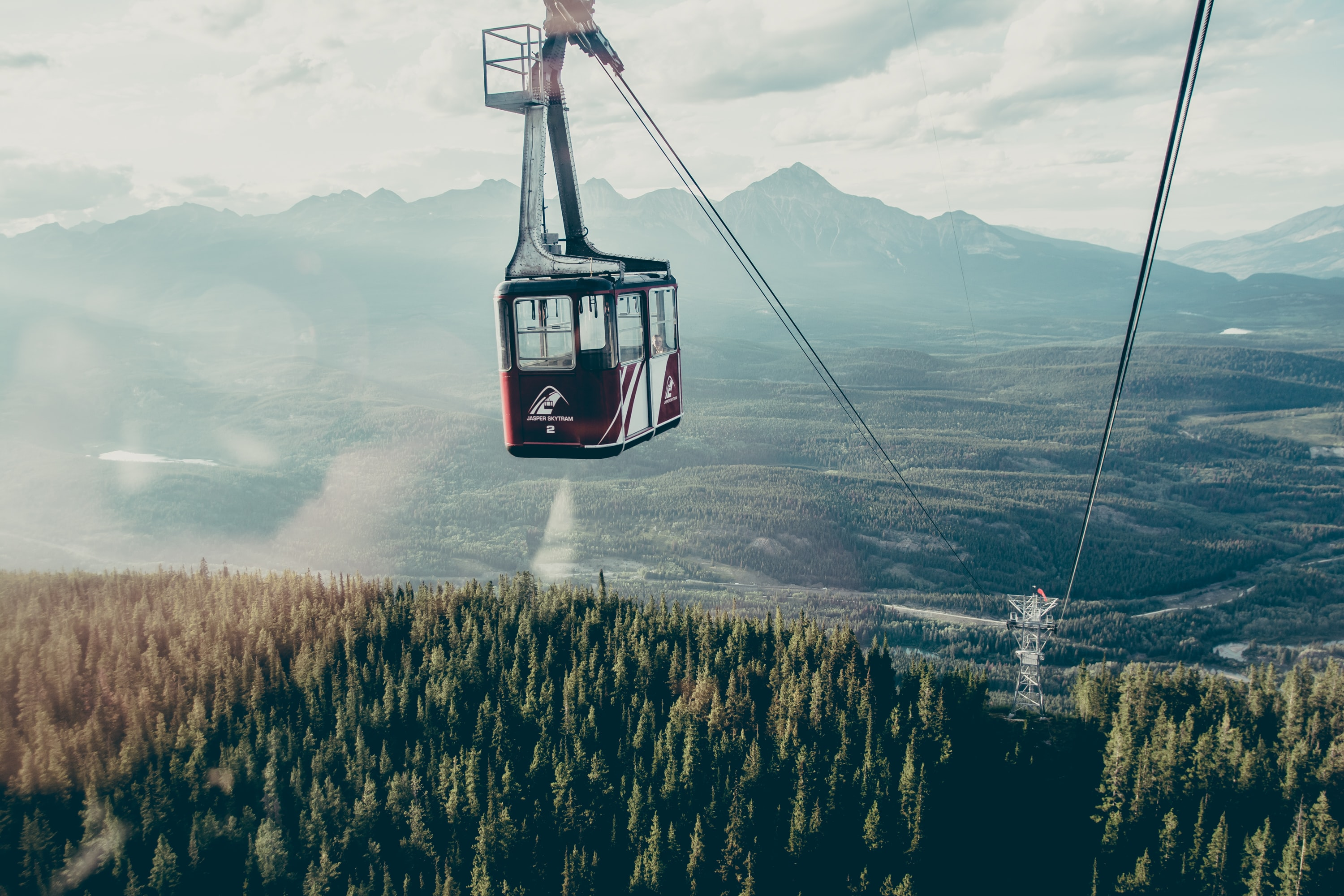 A gondola ski lift over an evergreen forest in the mountains