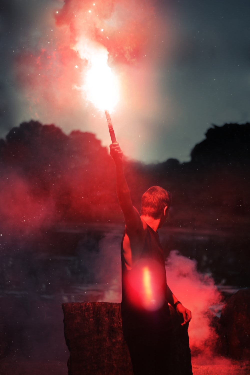 shallow focus photo of person holding flare
