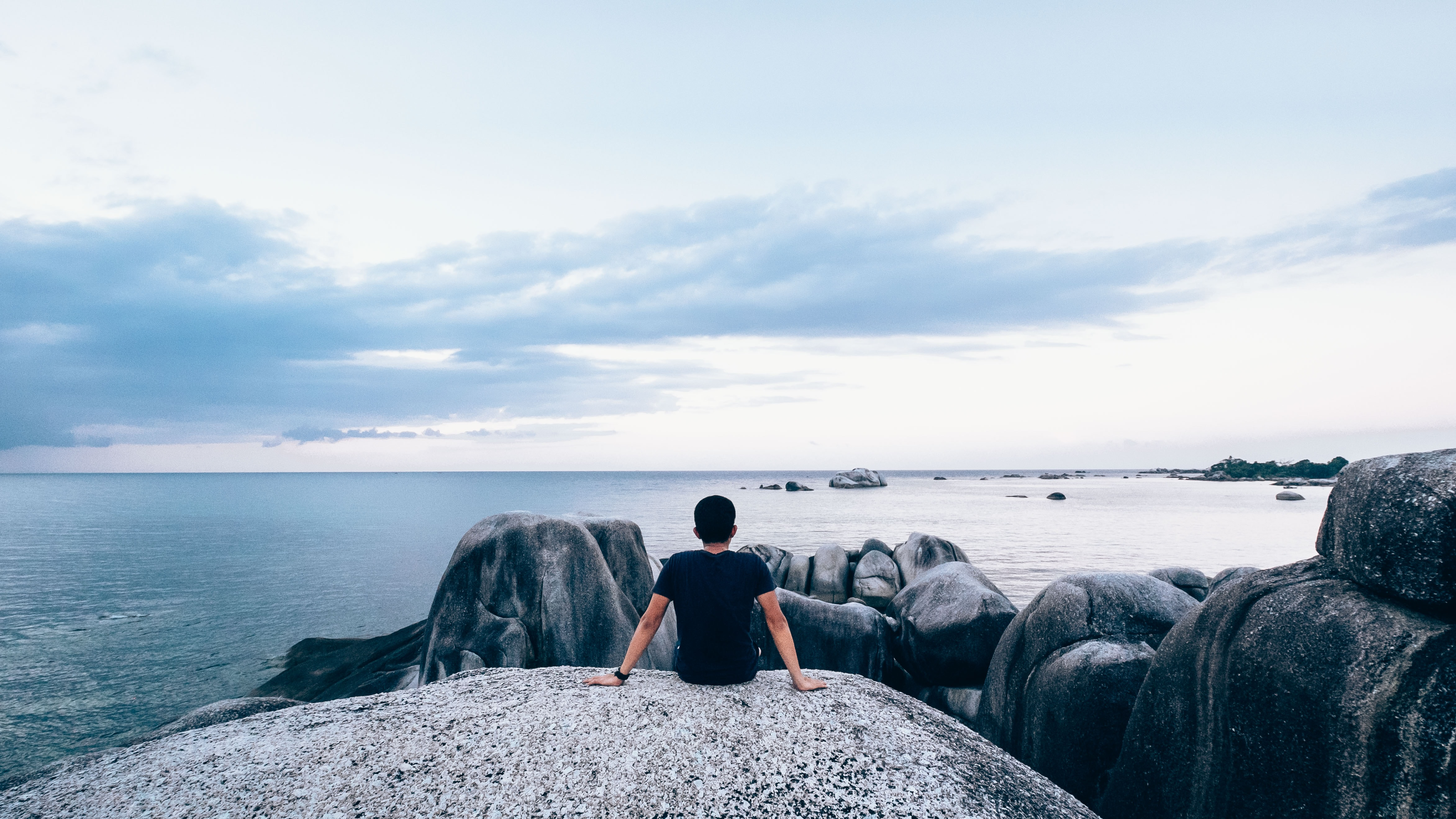 A man sits on a rock, overlooking rocks and the ocean, into the horizon.