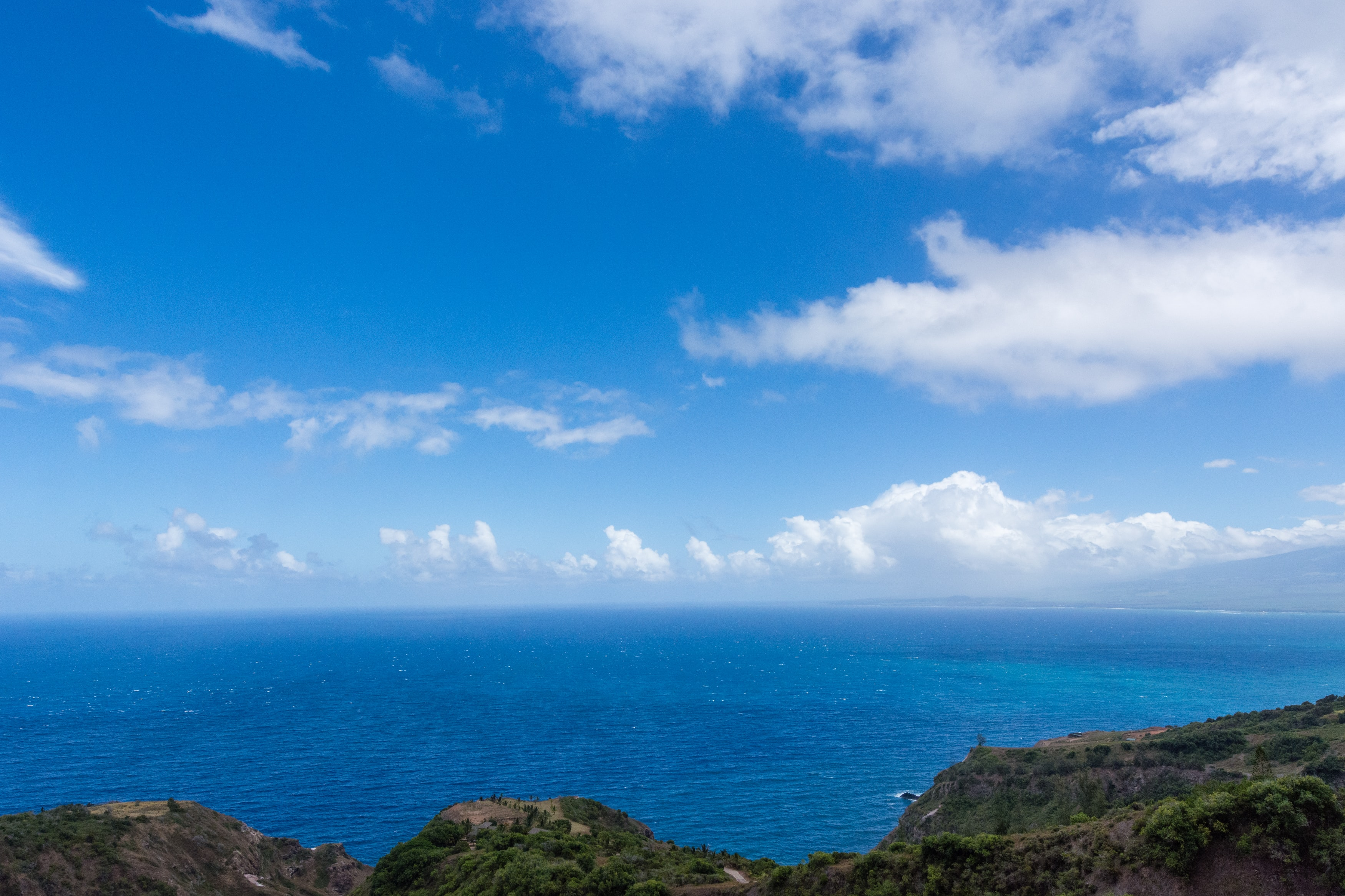 blue clouds above ocean near mountain panoramic photography
