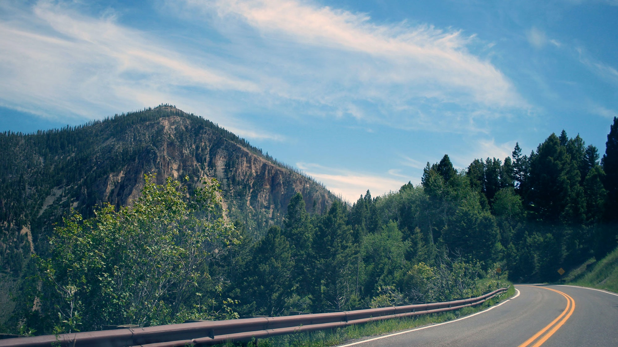 A mountain near a curve in a road in Yellowstone National Park