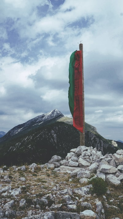 green and red flag on pile of rocks