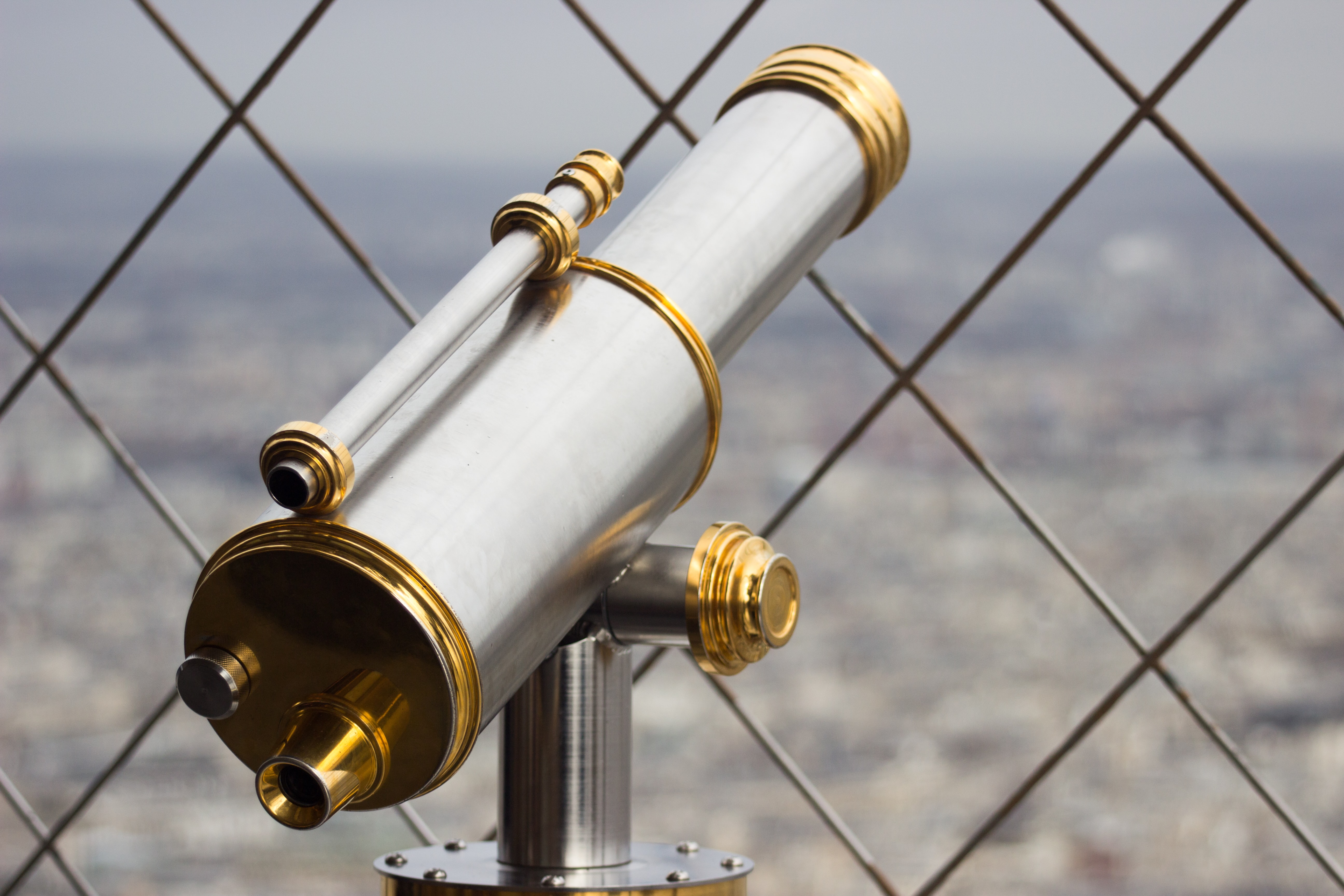 Sleek telescope peers through a chainlink fence over the city