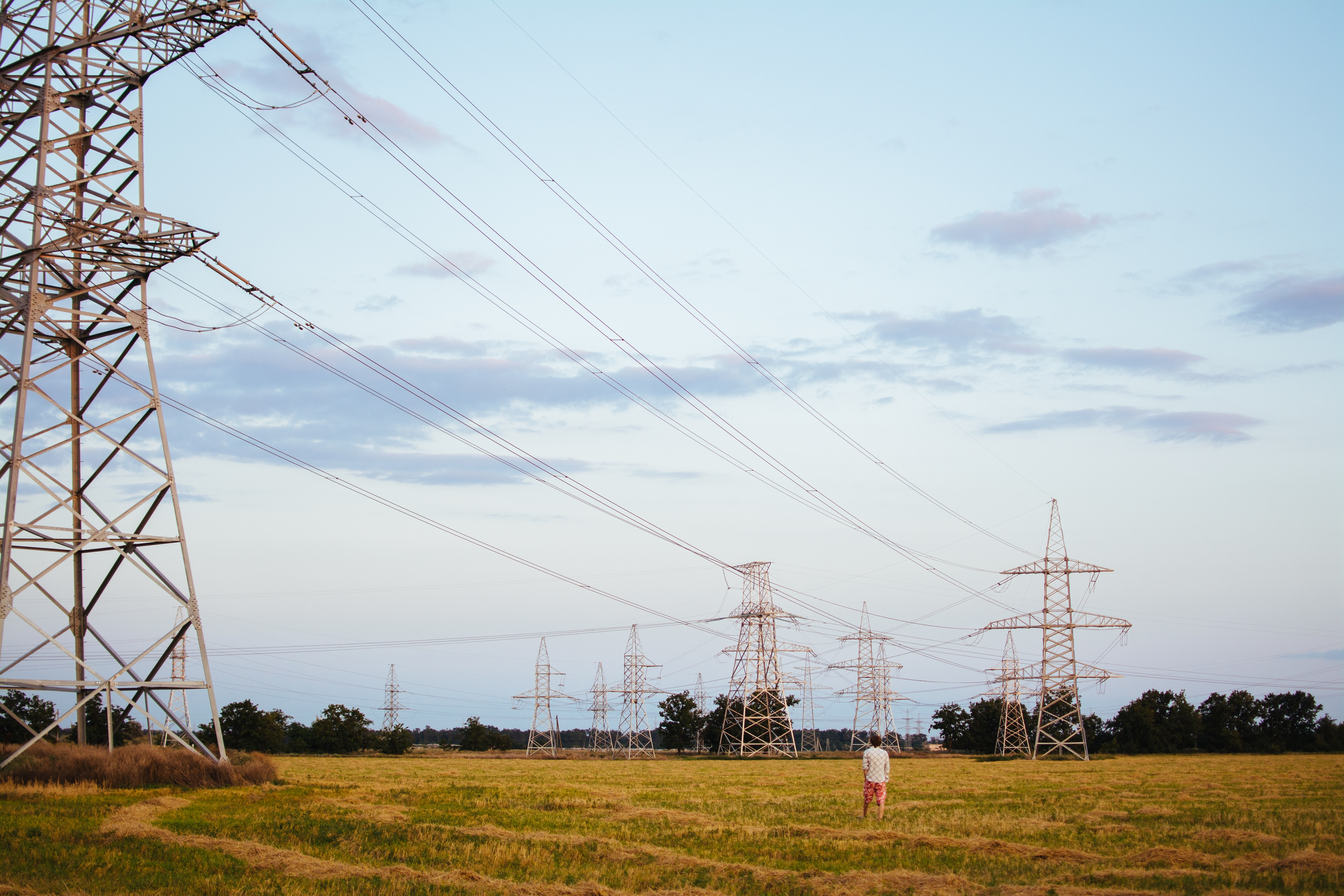 Man in a white shirt and red shorts standing in a field gazing at the pylons and power lines running between them under a slightly cloudy sky