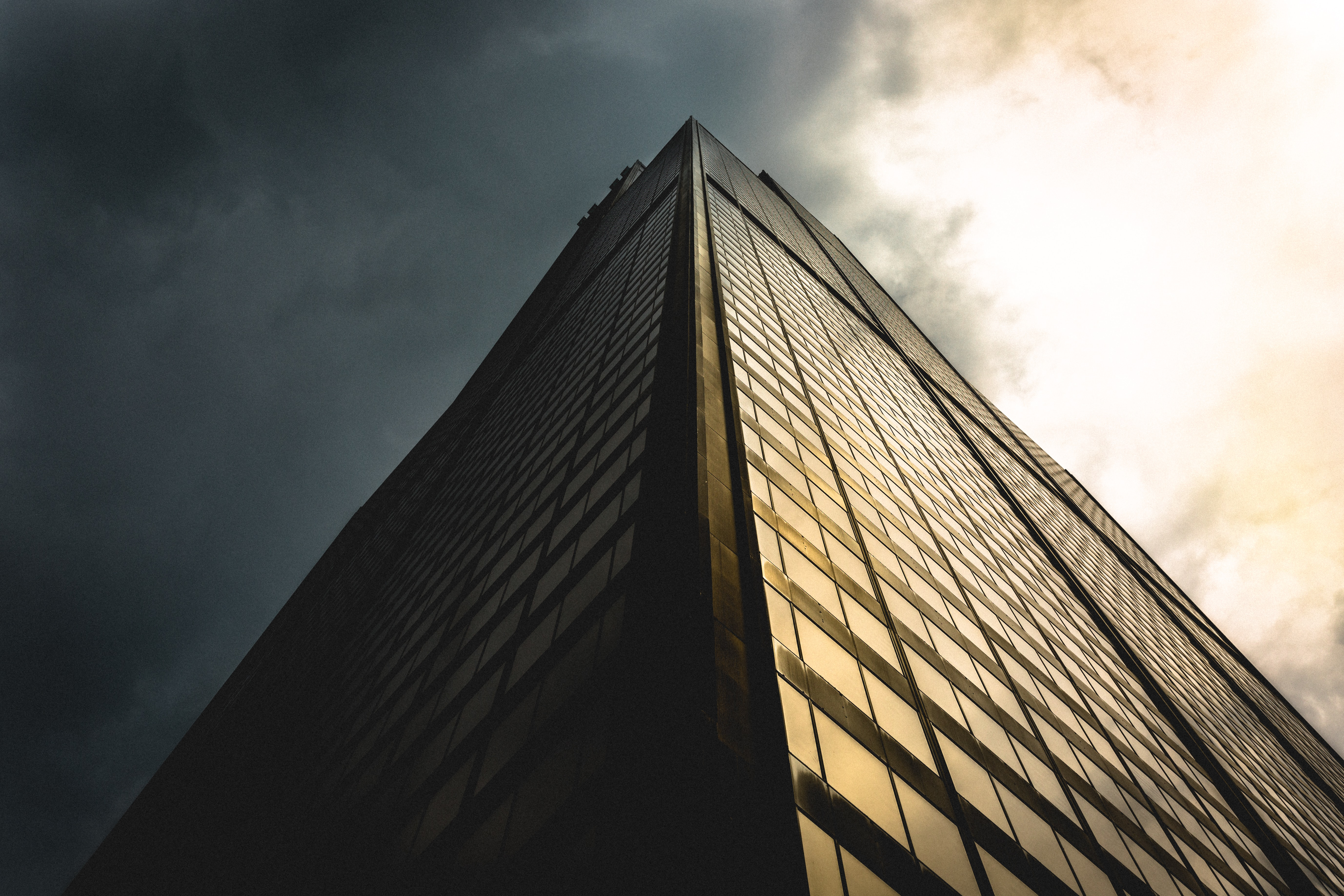 gray sky above black building low angle photography