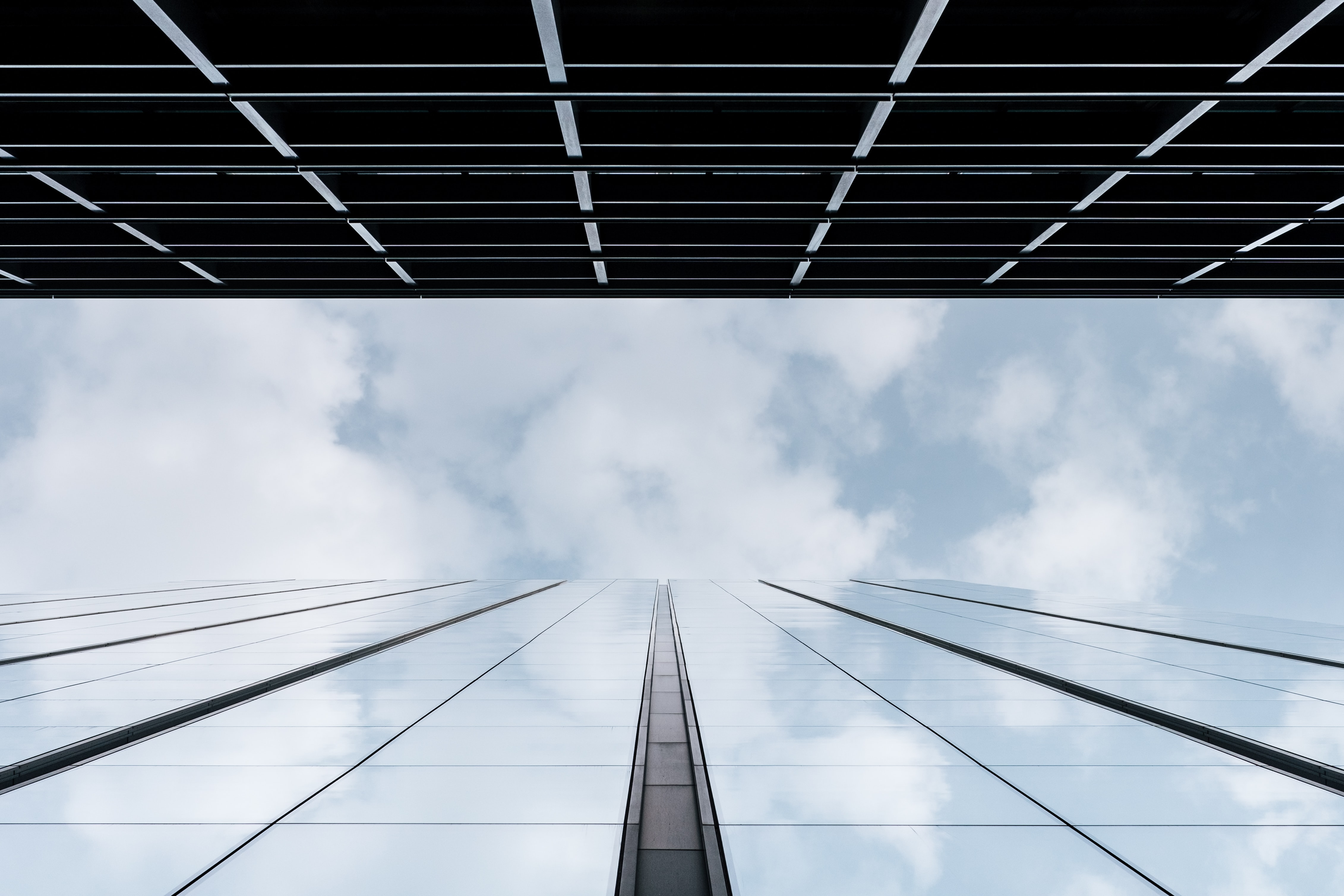 A low-angle shot of a glass facade reflecting the clouds in the sky above