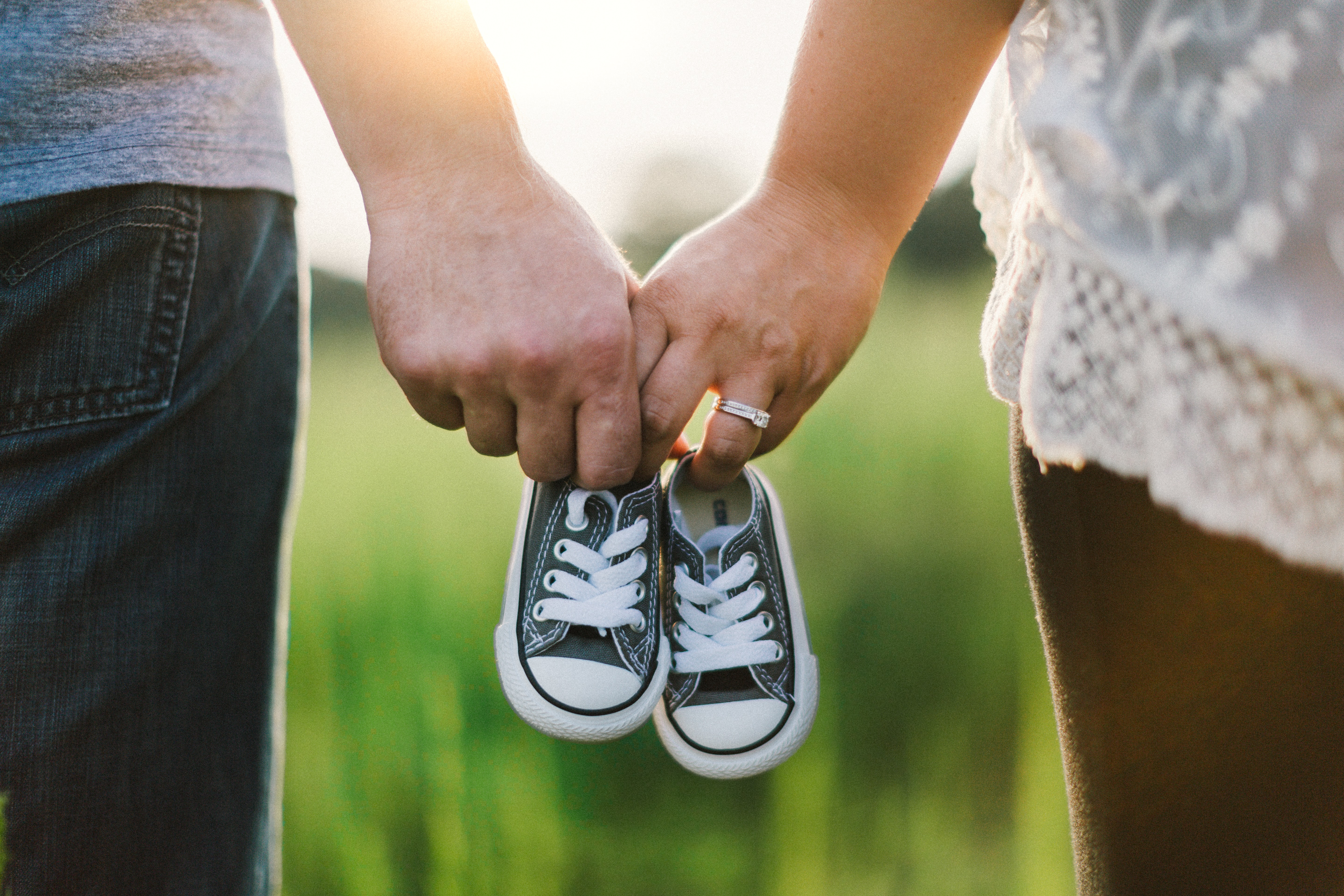 woman and man holding black crib shoes standing near green grass during daytime