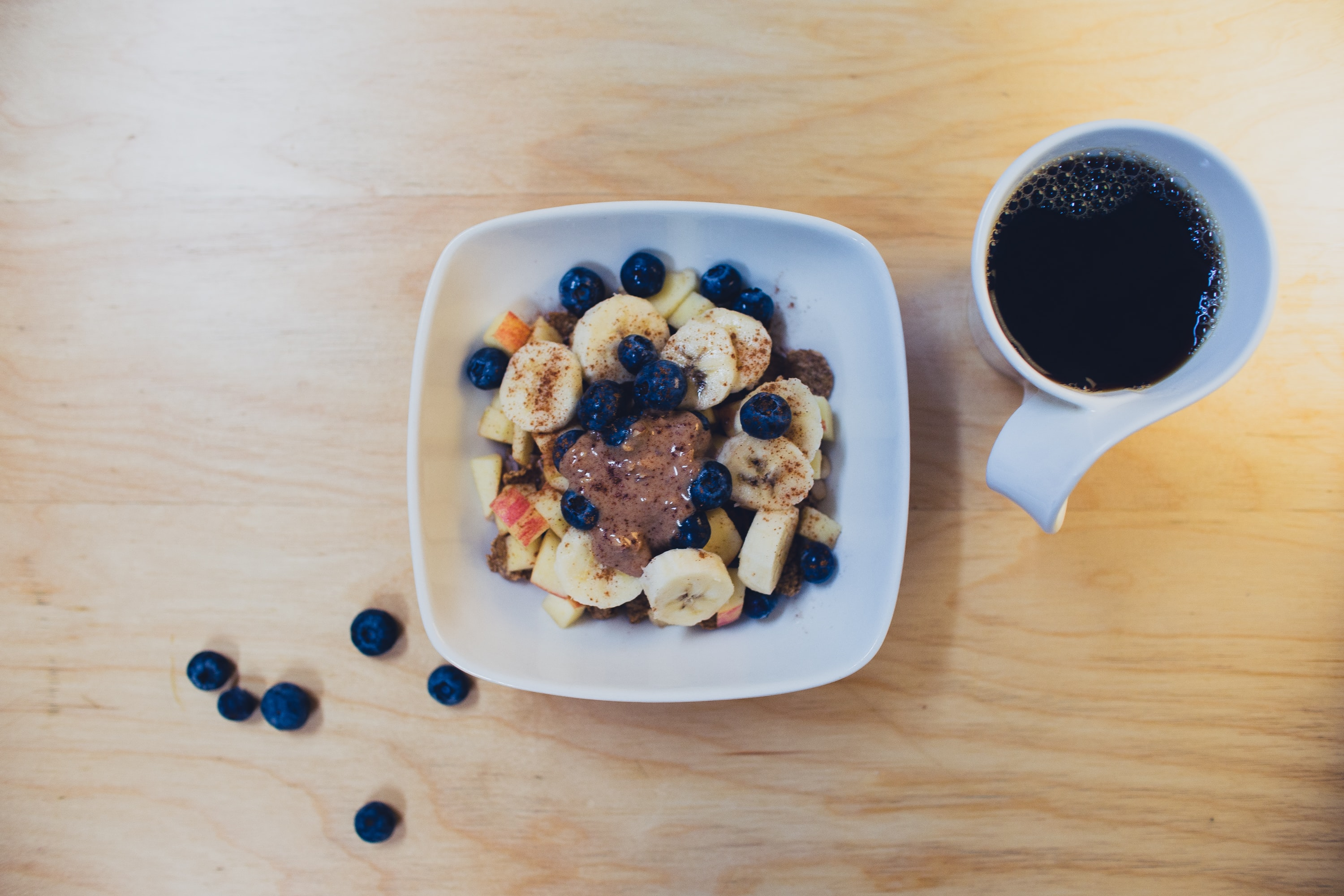An overhead shot of oatmeal with bananas and blueberries next to a cup of coffee