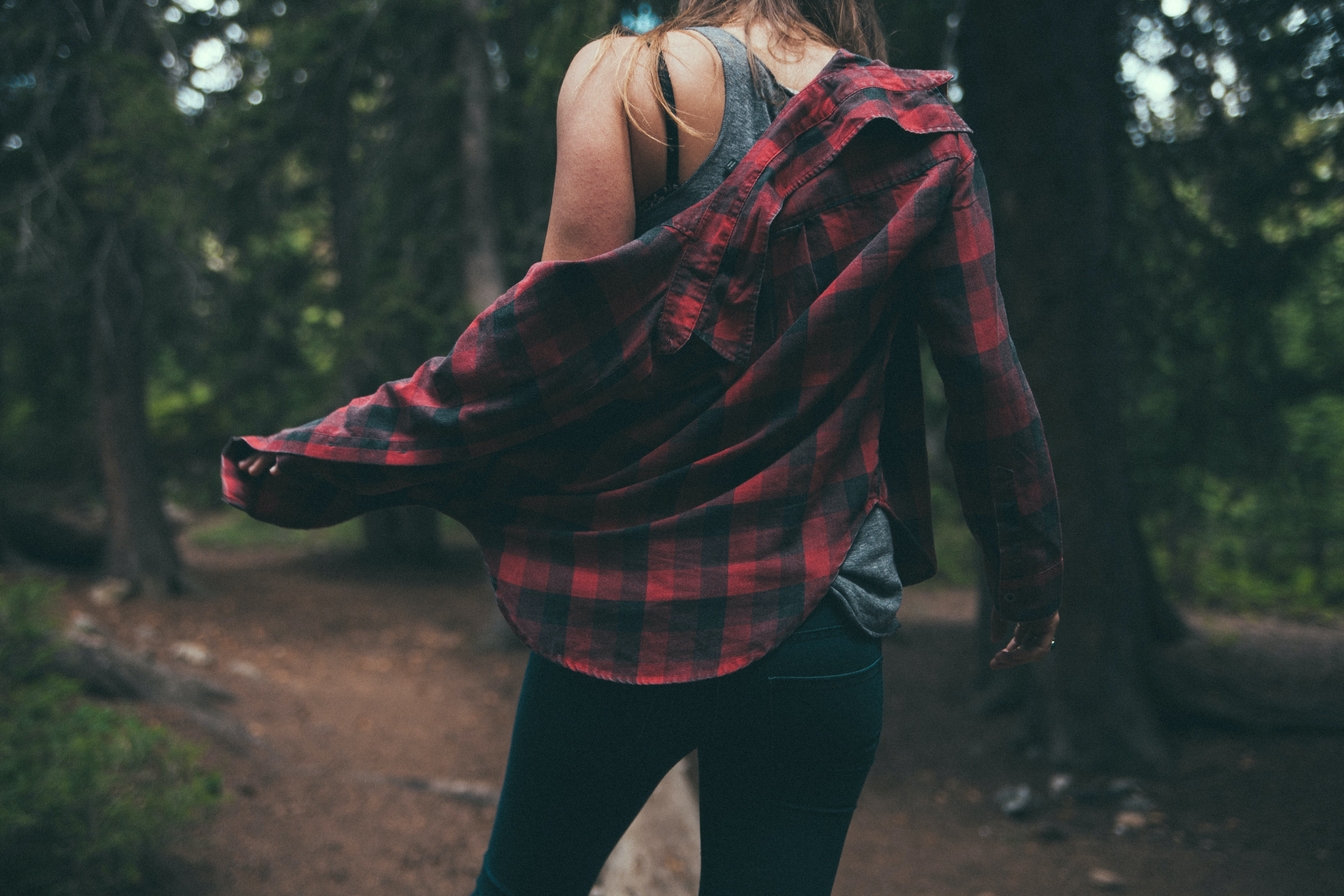 A woman taking off her flannel shirt in a forest