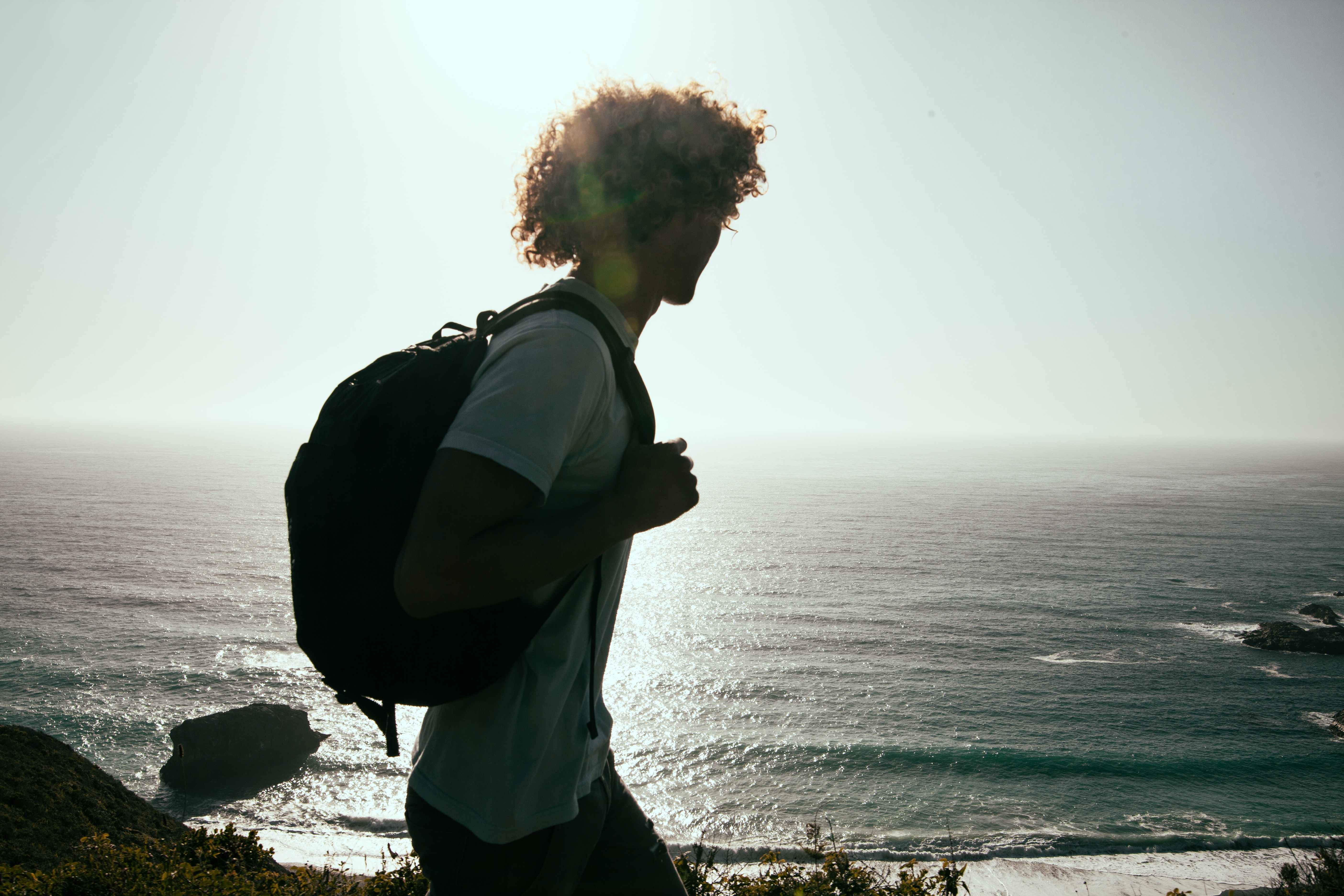 men wearing white-crew-neck t-shirt and black backpack watching the ocean