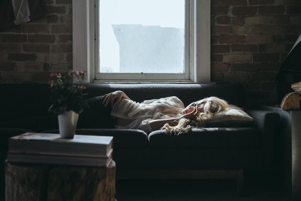 woman lying on sofa near closed window during daytime