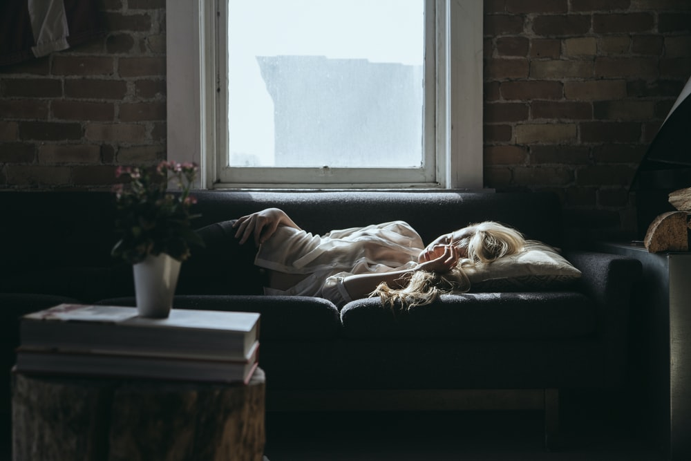 woman lying on sofa near closed window during daytime