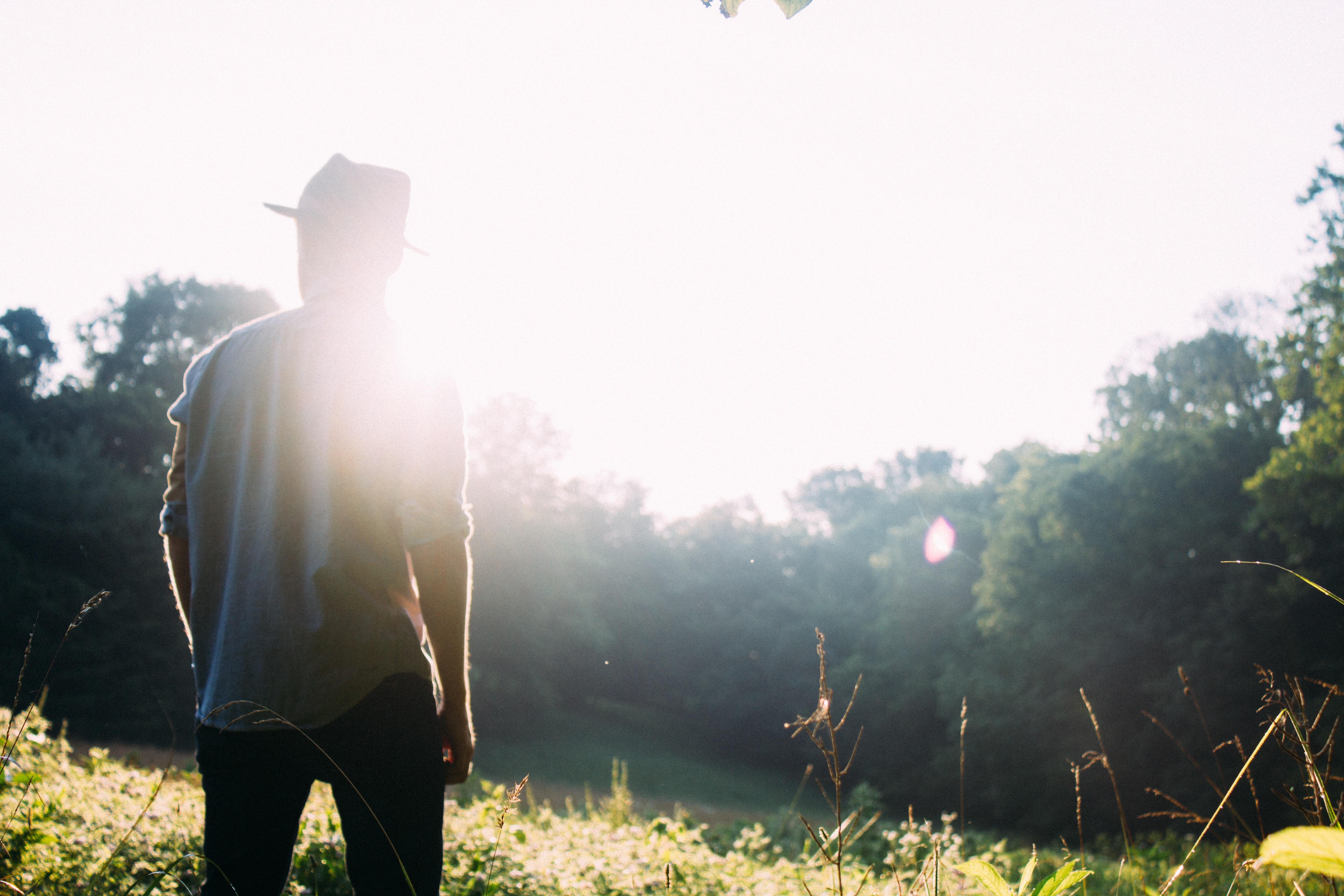 man standing on grass field with sun gazing