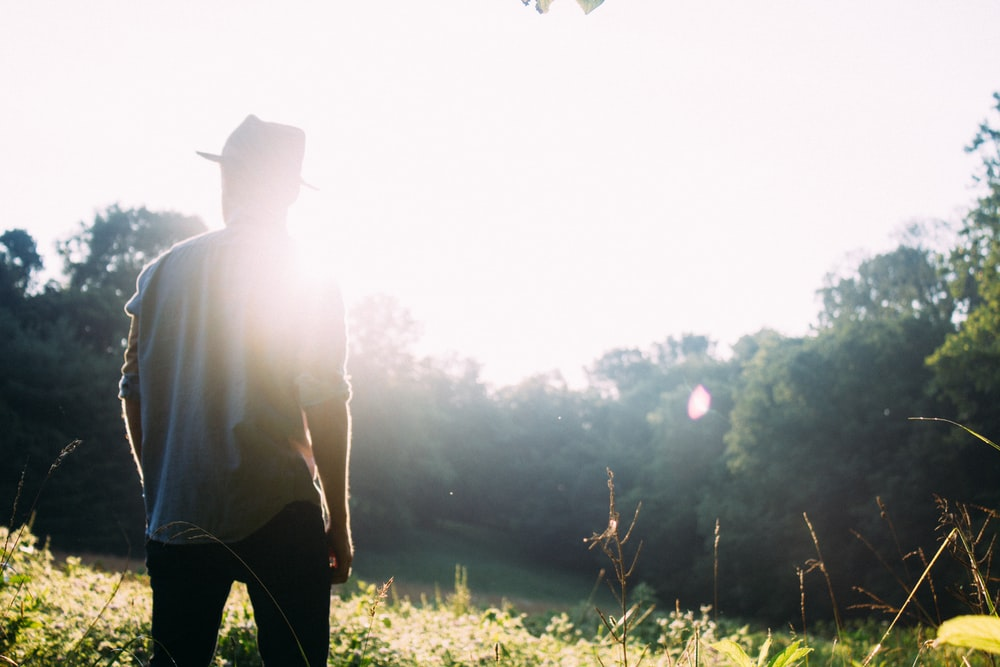 man standing on grass field with sun gazing
