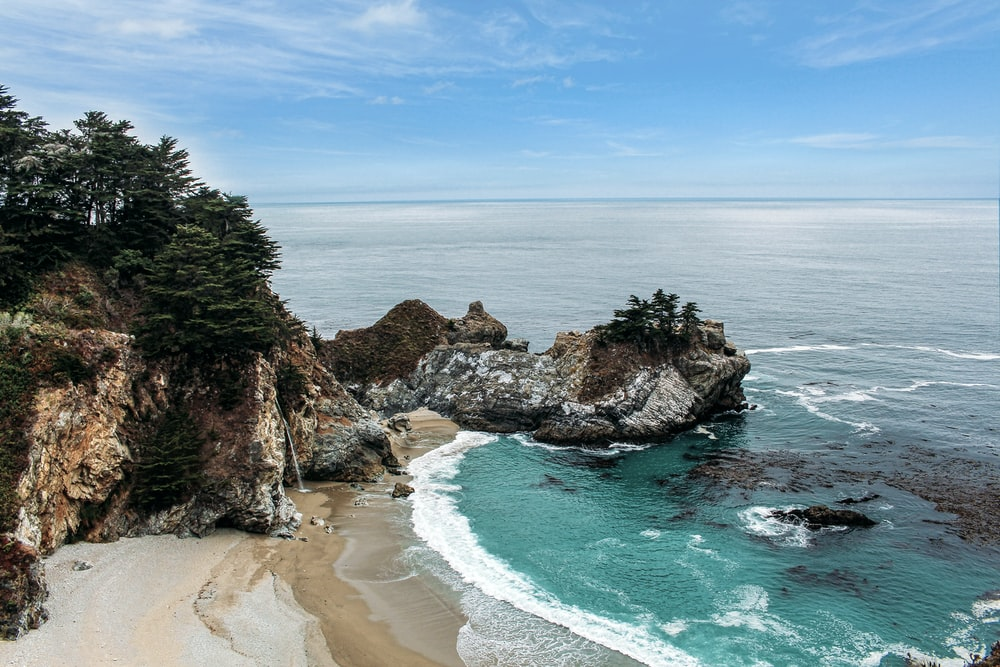 high-angle photo of green sea near white sand beach