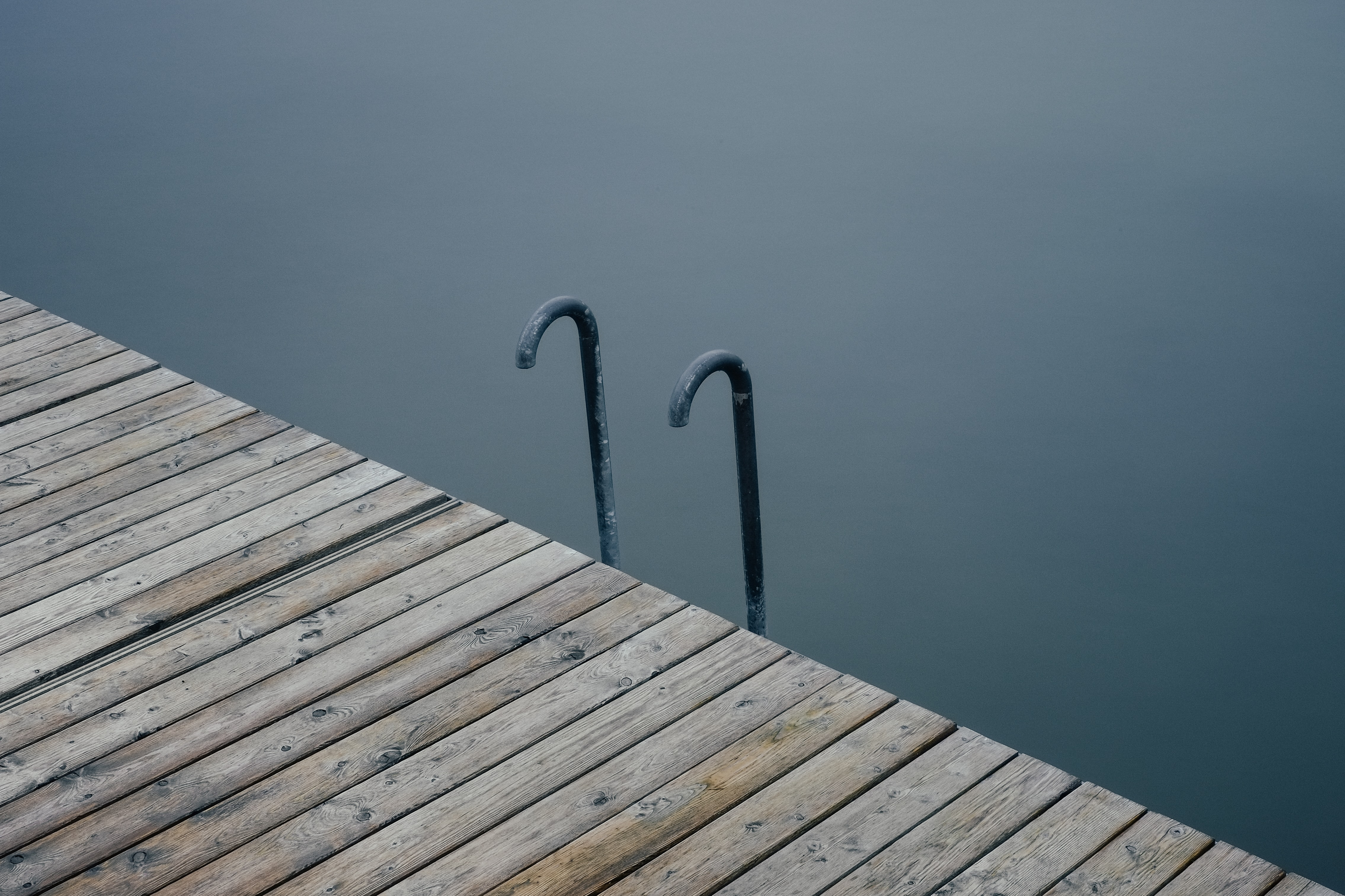 two black metal hooks near wooden dock