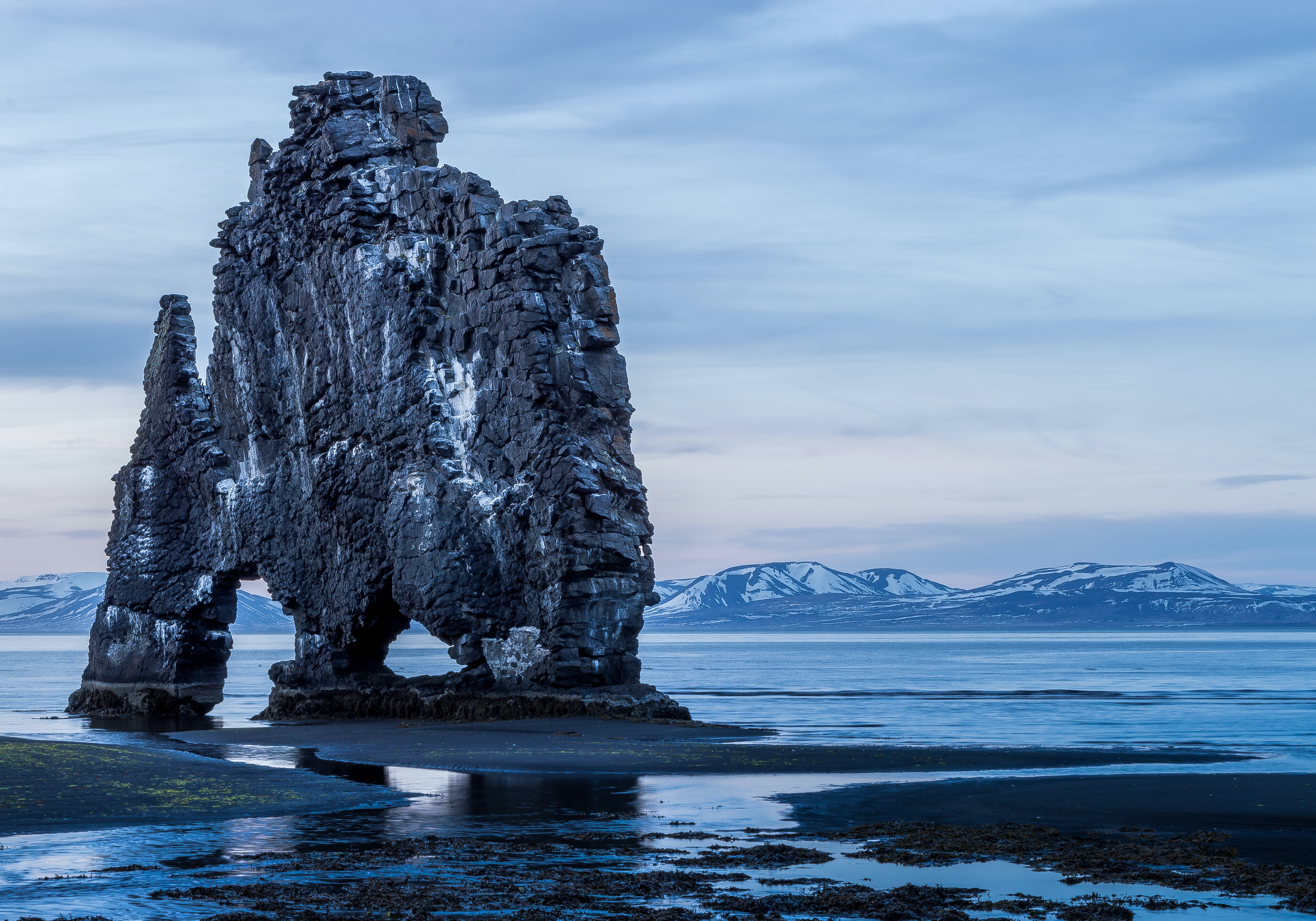 Tall rock formation above the ocean with snow covered mountains in the background at Hvítserkur