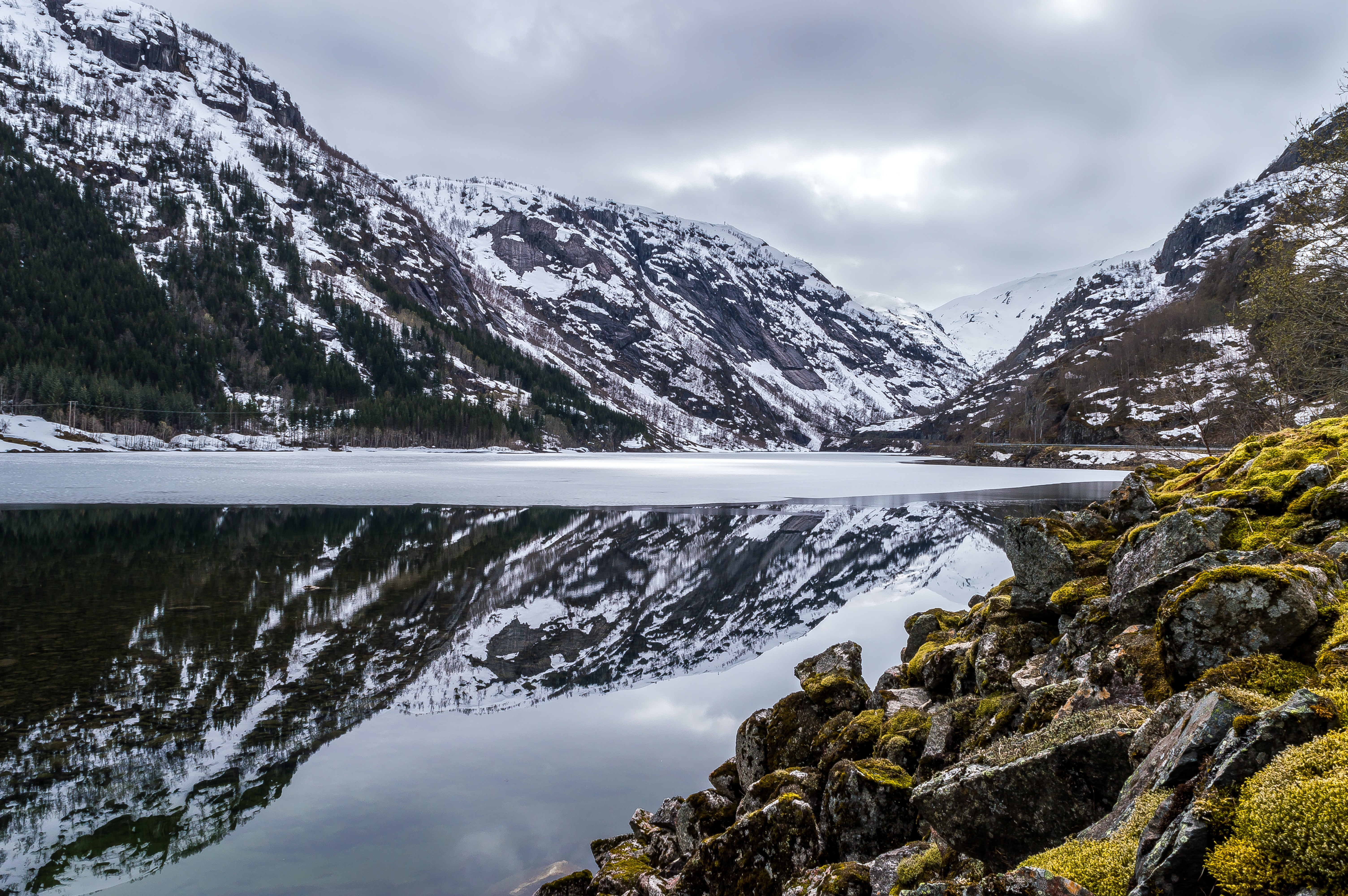 Snowy mountains on a cloudy day reflected  in a glassy, melting lake