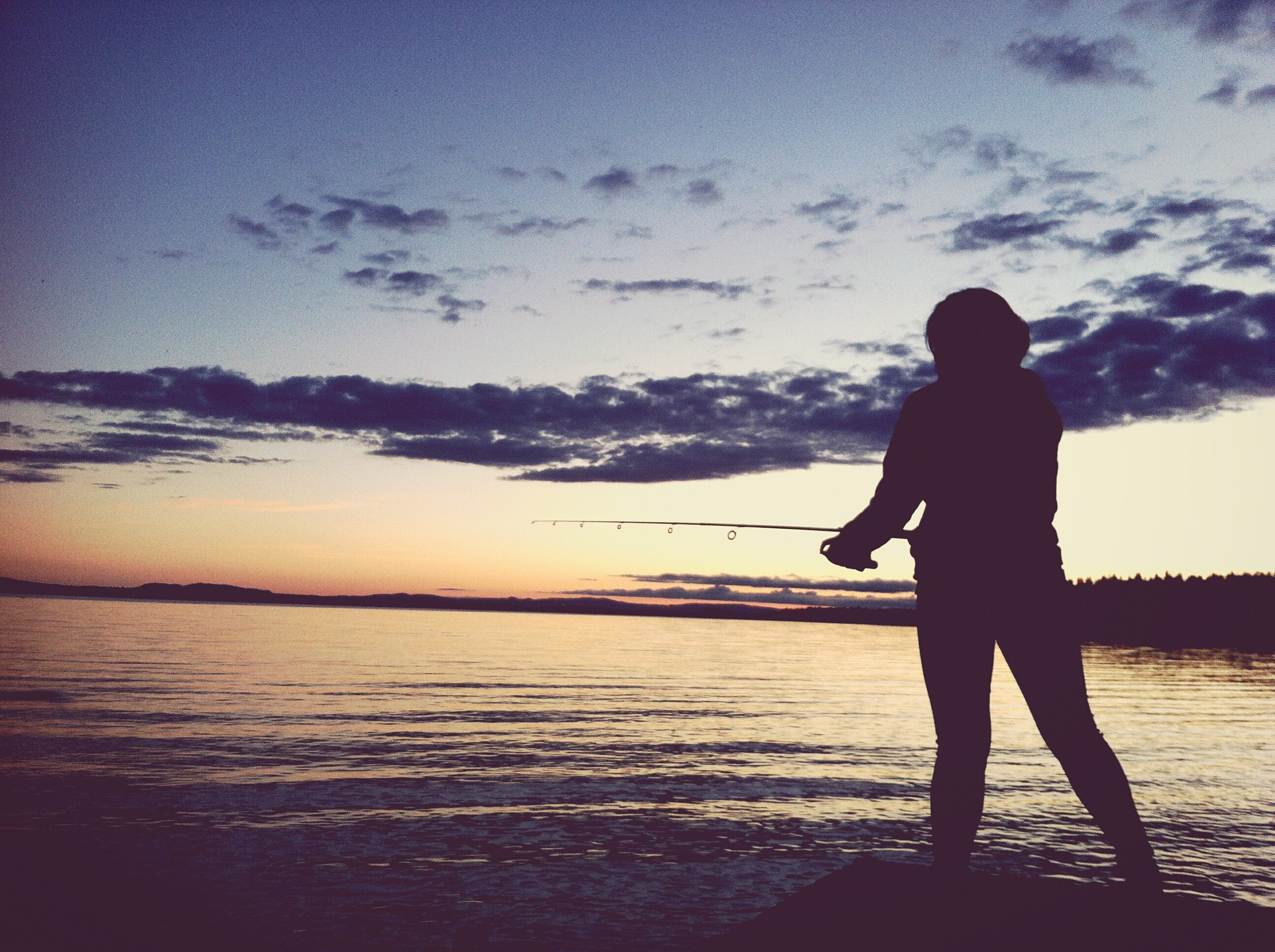 silhouette of person holding fishing rod taken at sunset