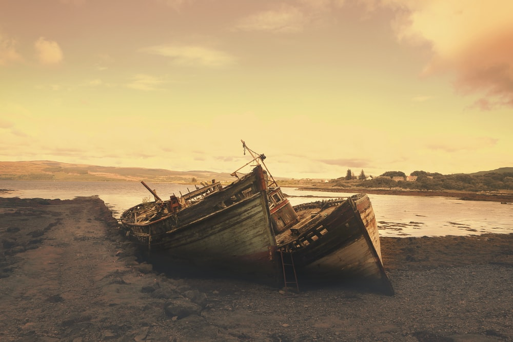 brown wreck boat near seashore during daytime