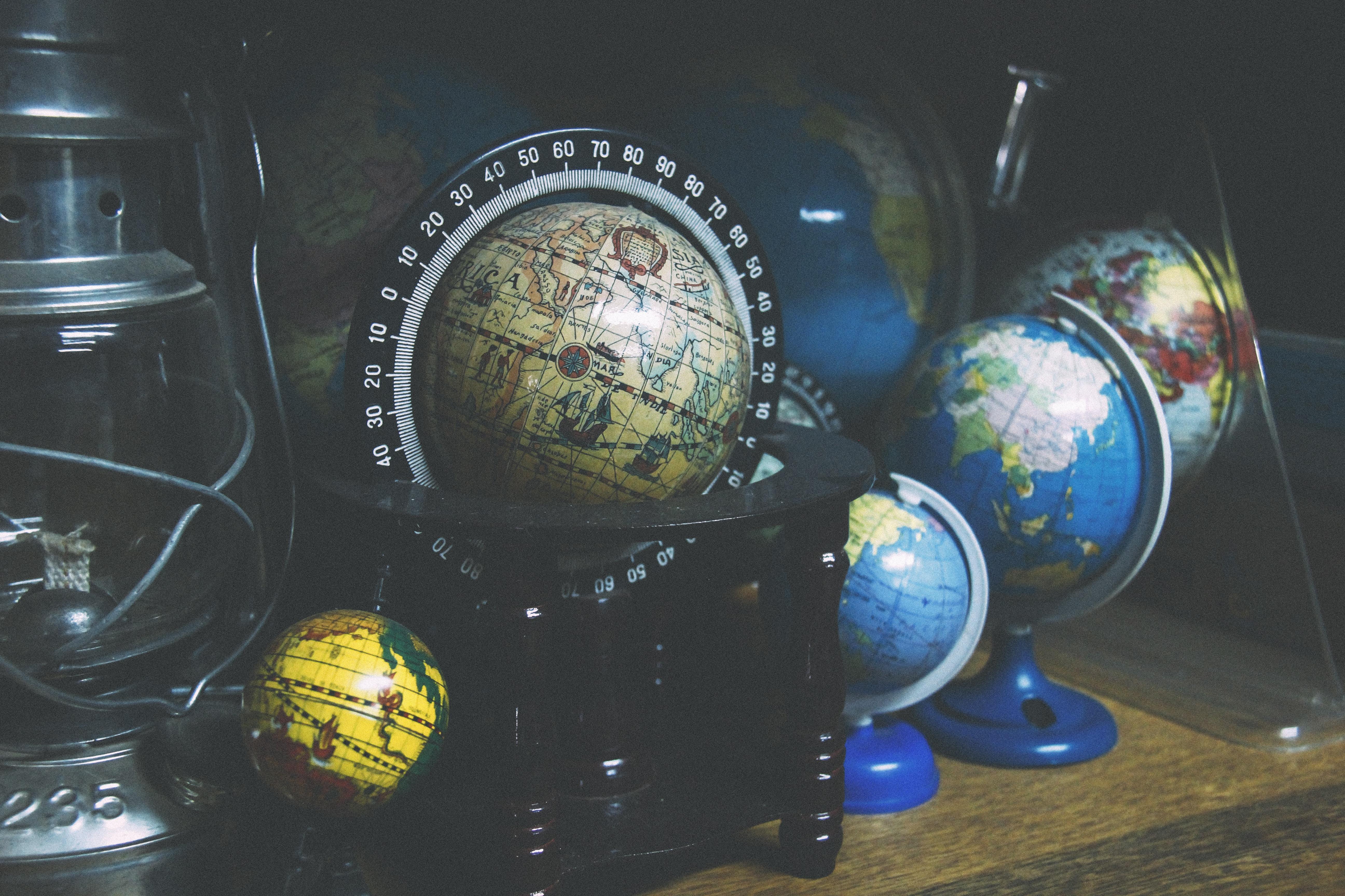 assorted mini desk globes on shelf near gray kerosene lantern