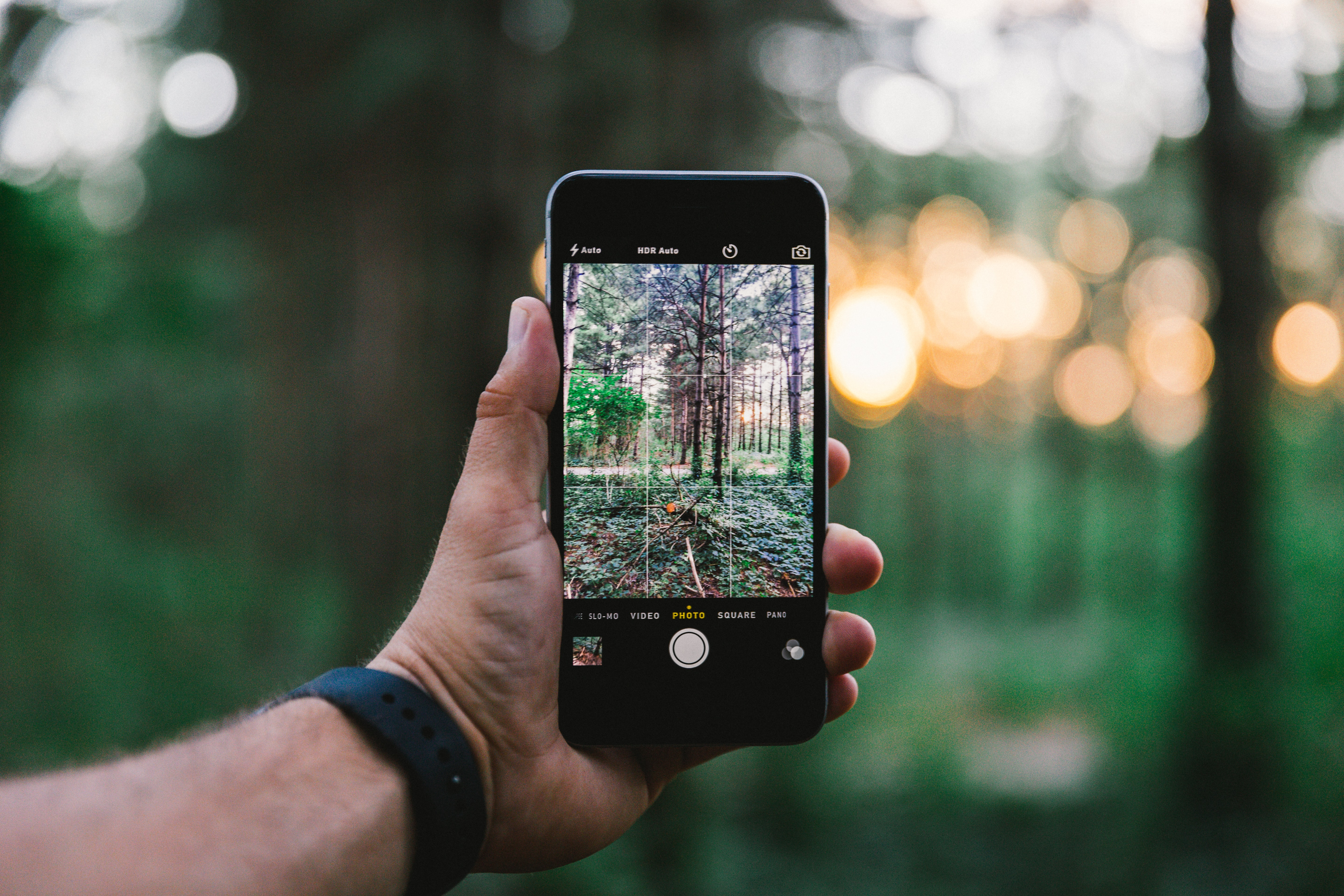 A man wearing a watch taking a photo of the forest with his iPhone cellphone at Big Woods Lake